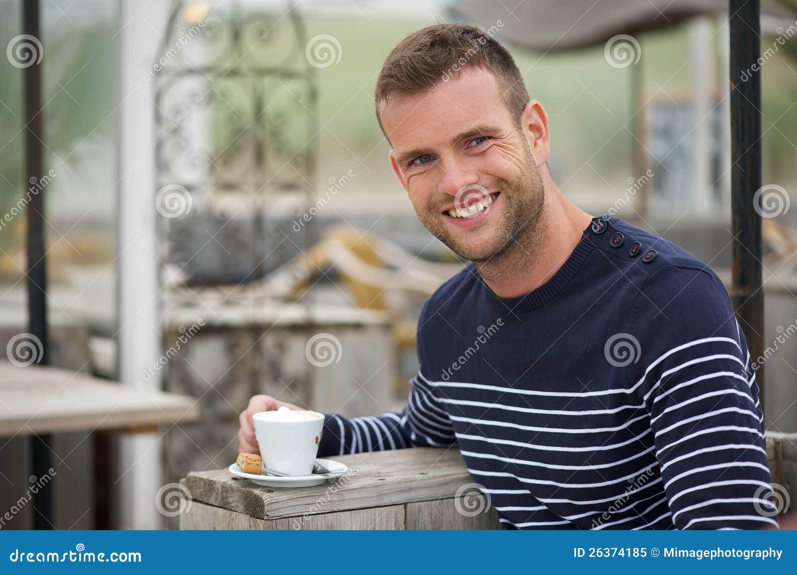 Junger Mann, der mit seinem Kaffee an einem Strand-Kaffee lächelt