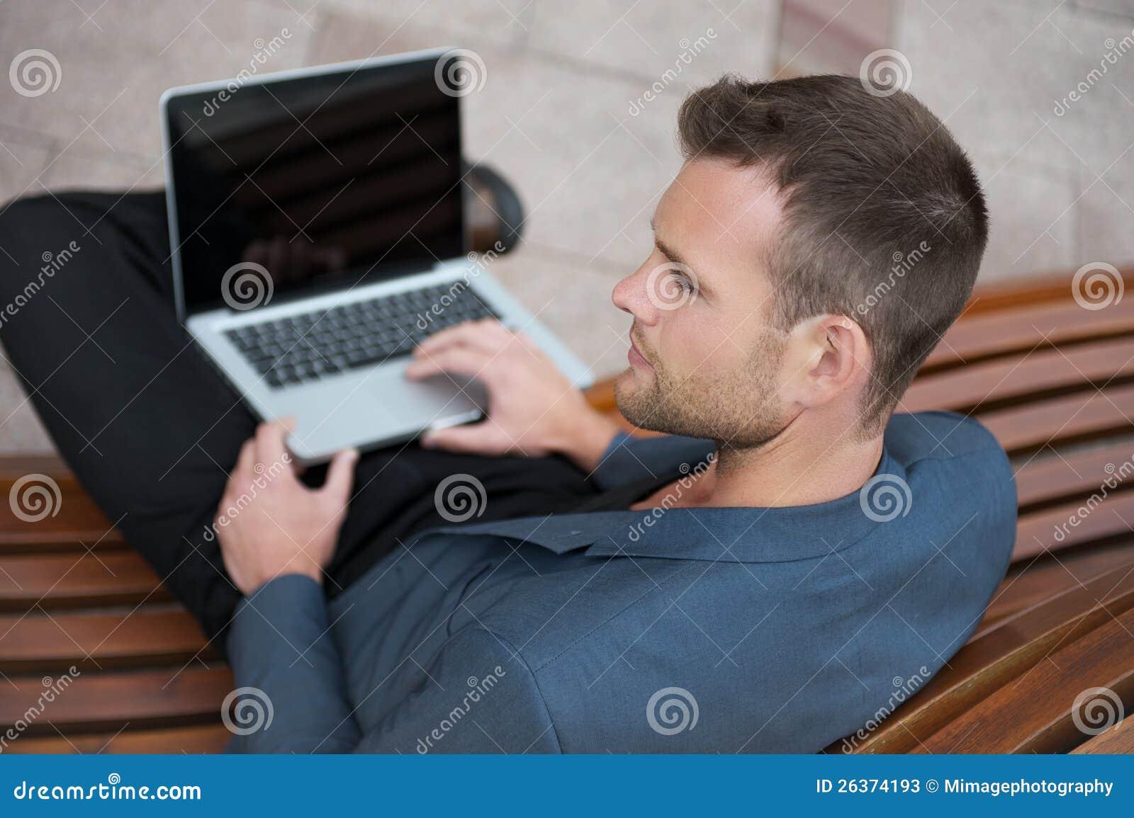 Junger Mann, der mit seinem Laptop sitzt