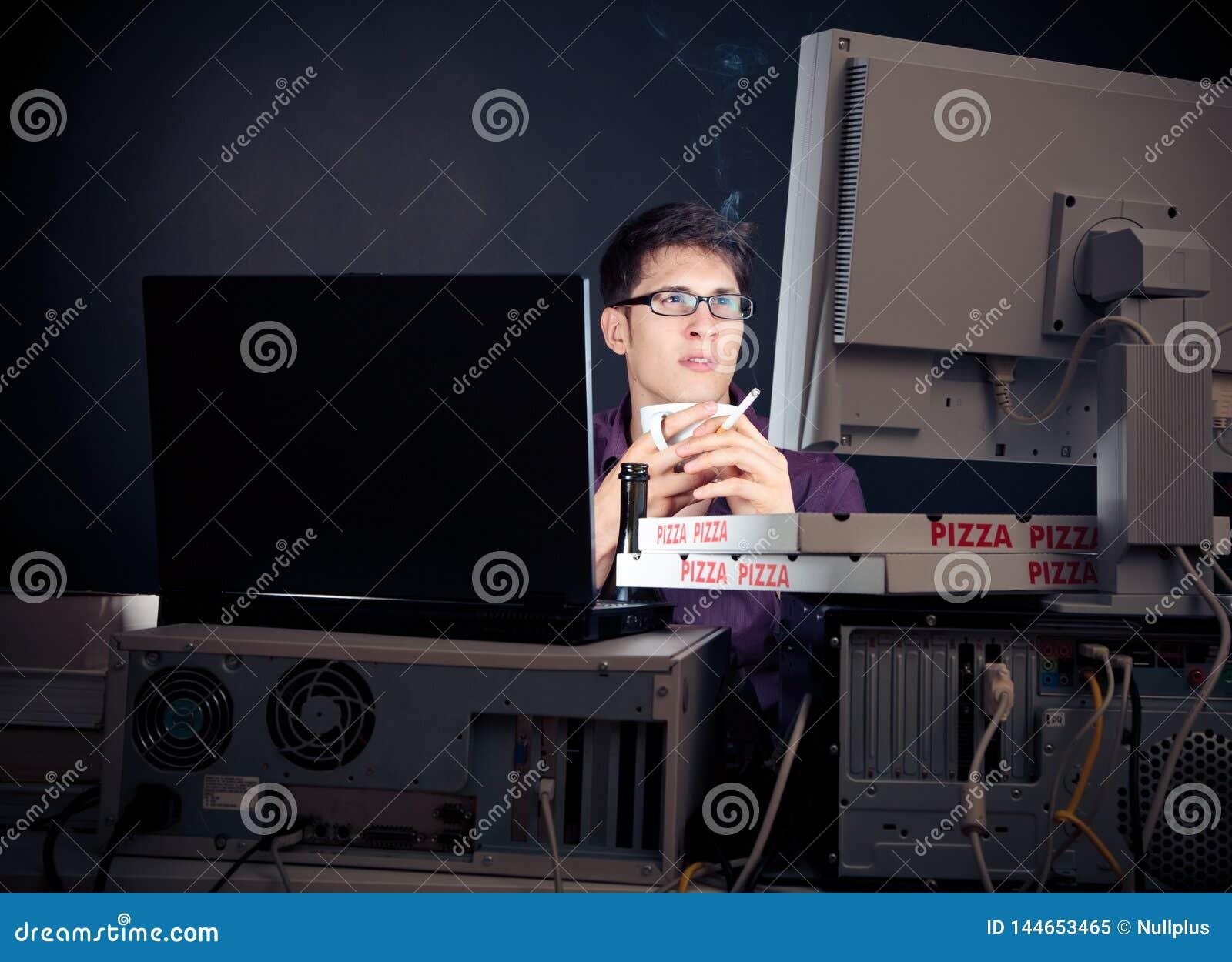 Junger Mann, der seine Nacht mit Computern verbringt