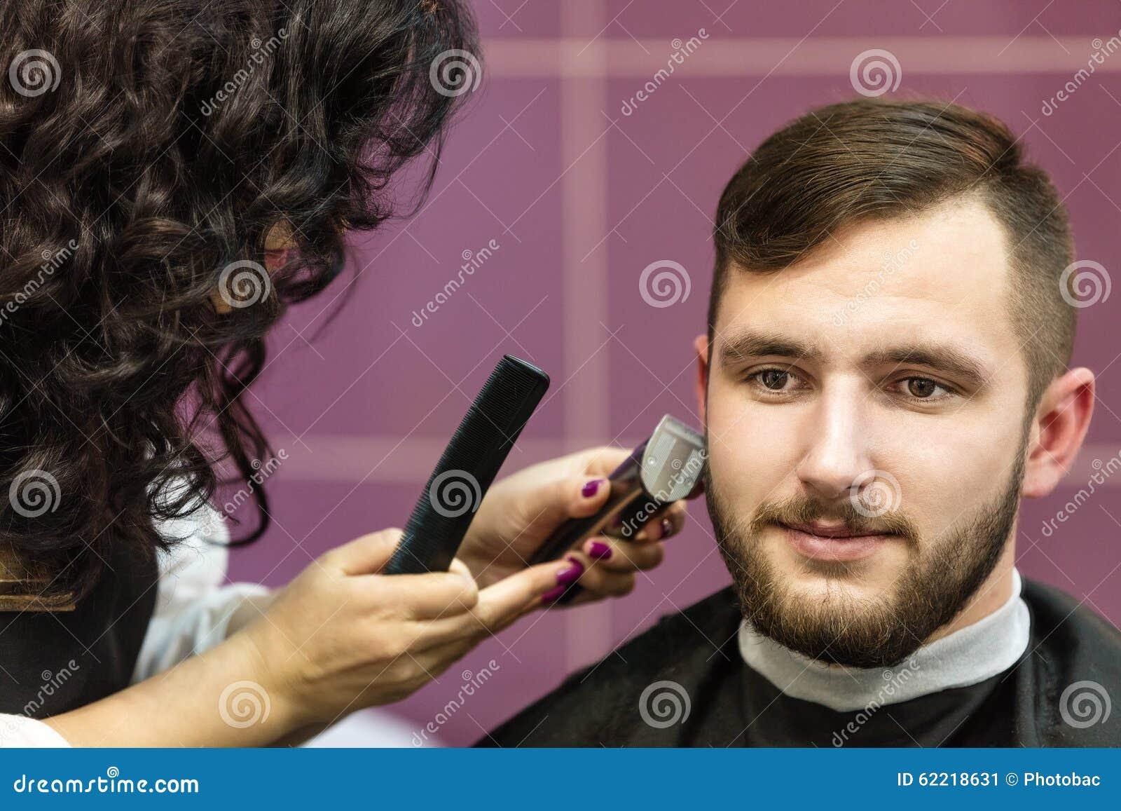 Junger Mann, der seinen Bart sich pflegen lässt