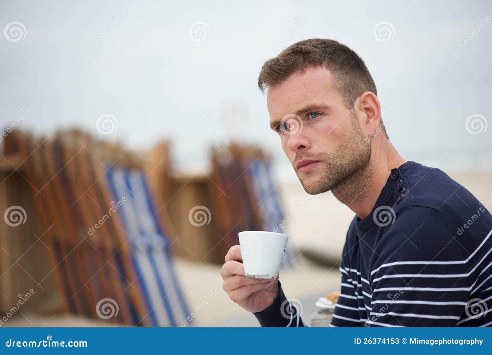 Junger Mann, der seinen Kaffee am Strand trinkt