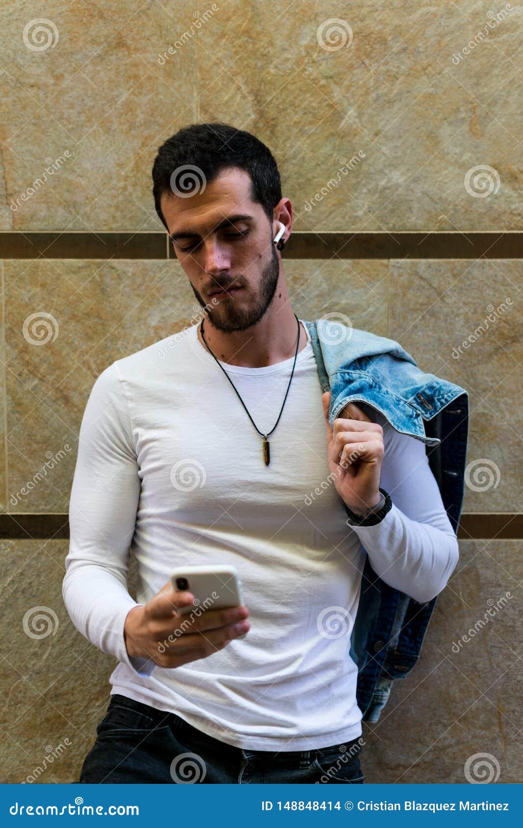 Junger Mann, der Smartphone in der Stra?e schaut Moderner Hintergrund