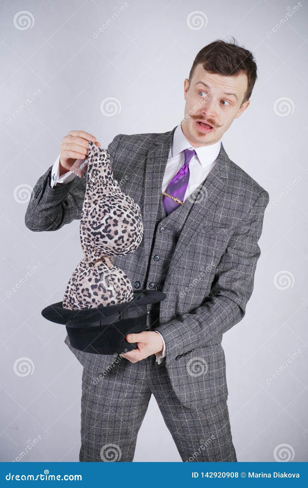 Junger Mann in einem Anzug zieht Leopard-BH von seinem Hut aus, aber er wünschte Tricks mit Wunder und Reichtum emotionaler Mann