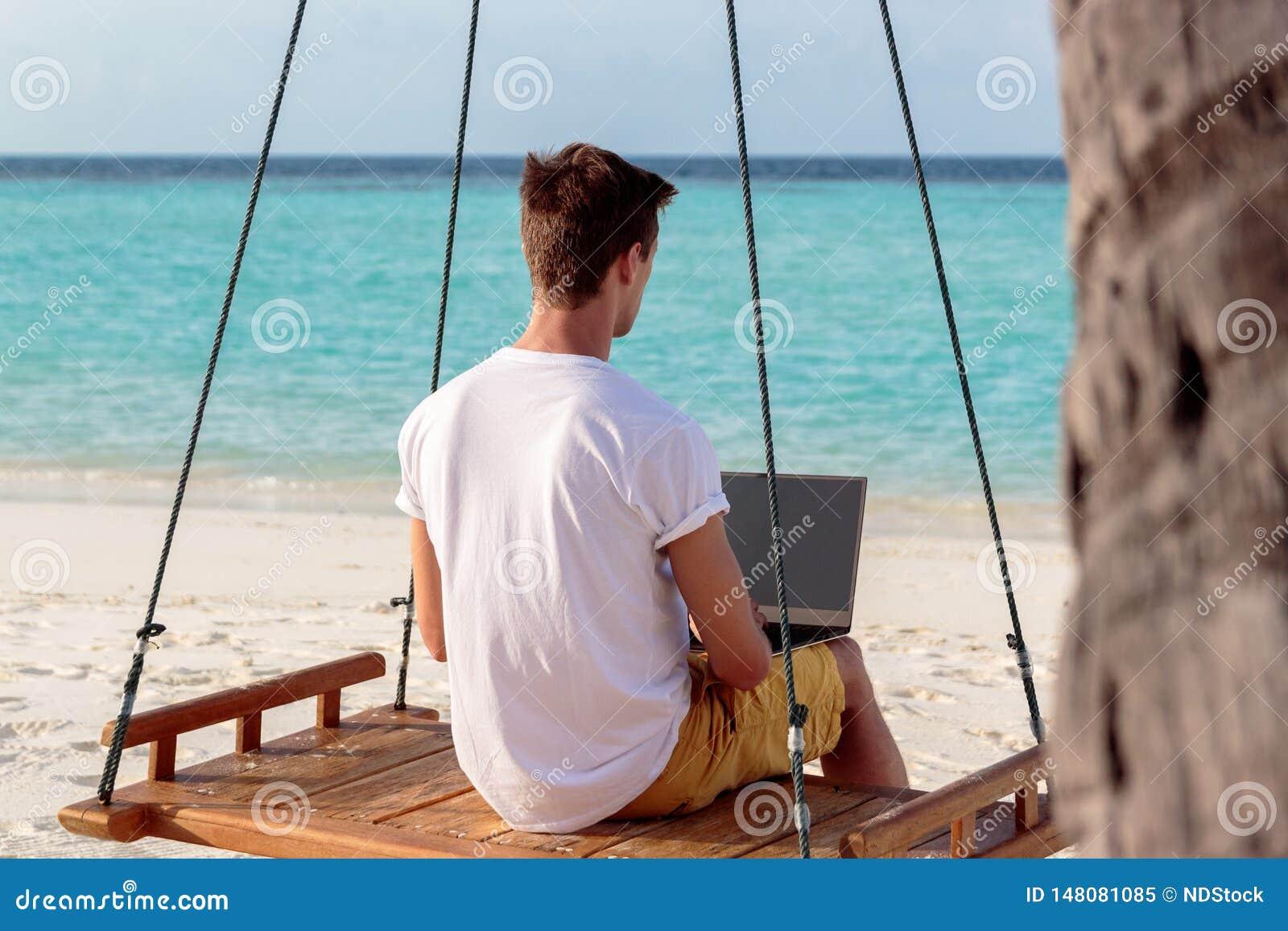 Junger Mann gesetzt auf einem Schwingen und dem Arbeiten mit seinem Laptop Klares blaues tropisches Wasser als Hintergrund