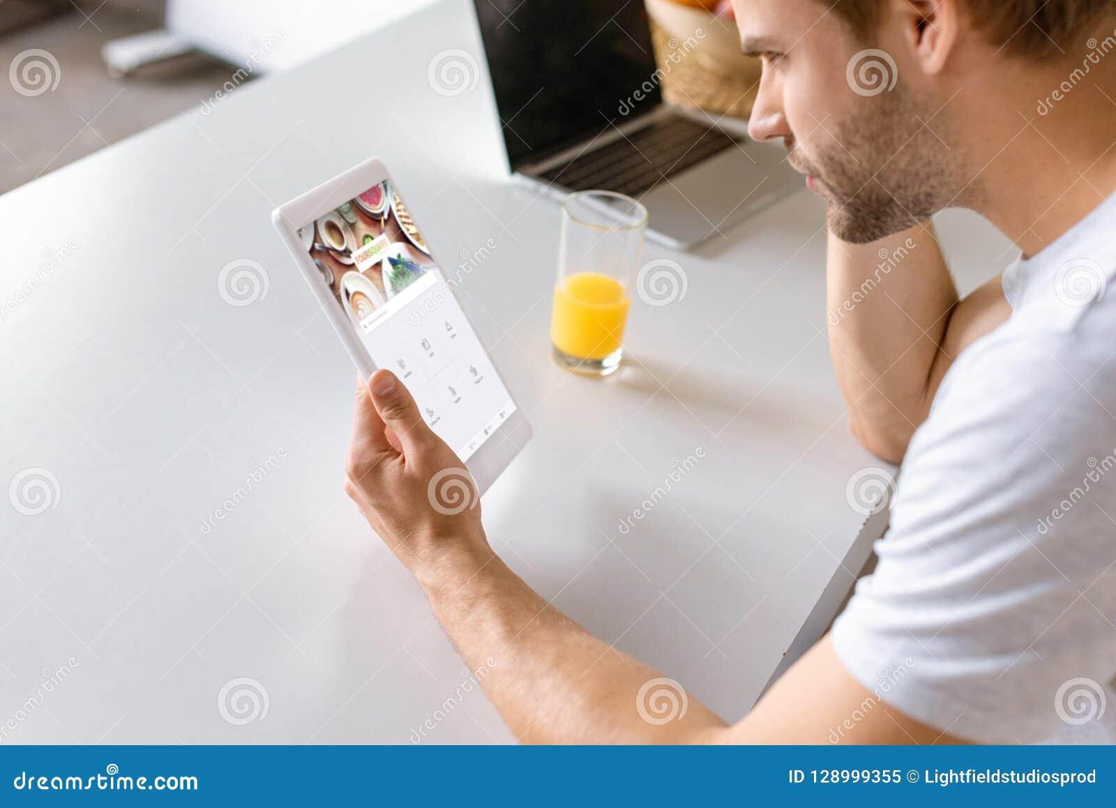 Junger Mann am Küchentisch mit Saft und Laptop unter Verwendung der digitalen Tablette mit foursquare