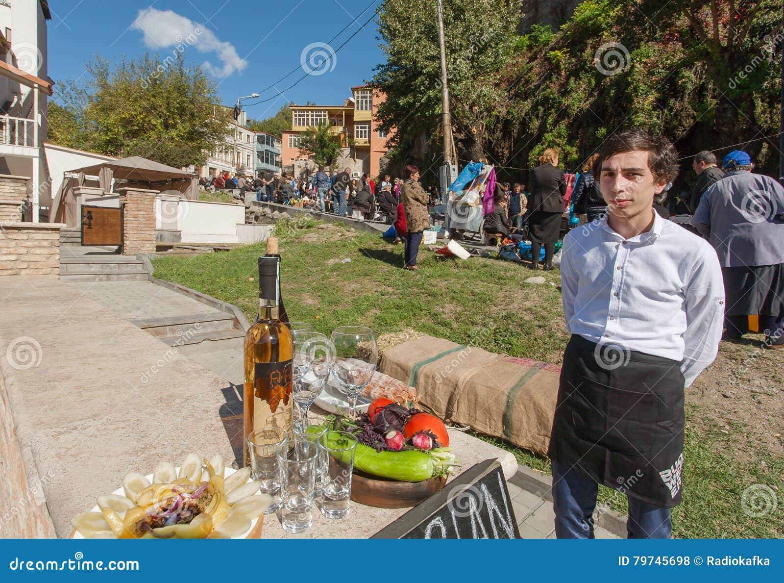 Junger Mann lädt Touristen für schmeckendes Chacha, traditionelles alkoholisches Getränk ein