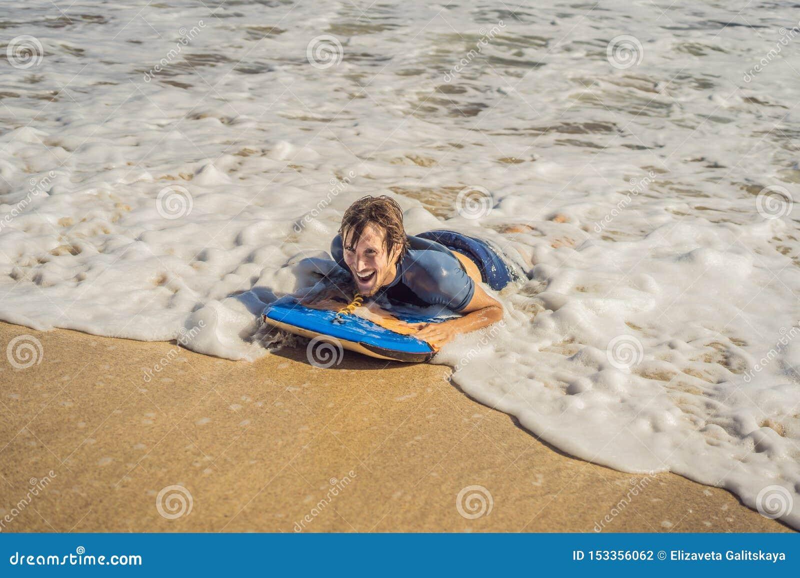 Junger Mann mit Boogie-Brett am Strand