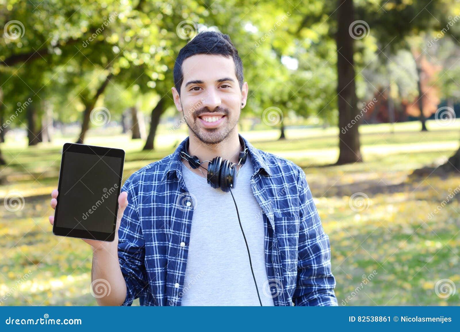 Junger Mann mit den Kopfhörern, eine Tablette halten