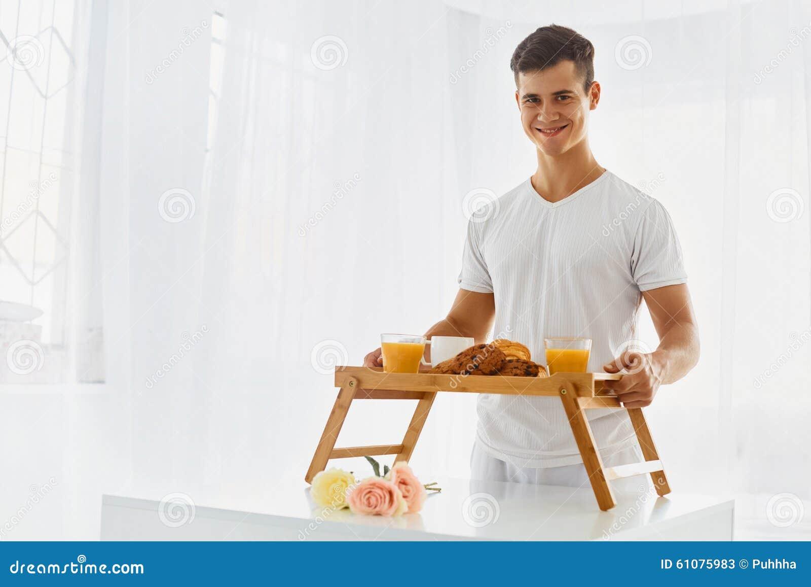 junger mann mit fr hst ck im bett stockfoto bild 61075983. Black Bedroom Furniture Sets. Home Design Ideas