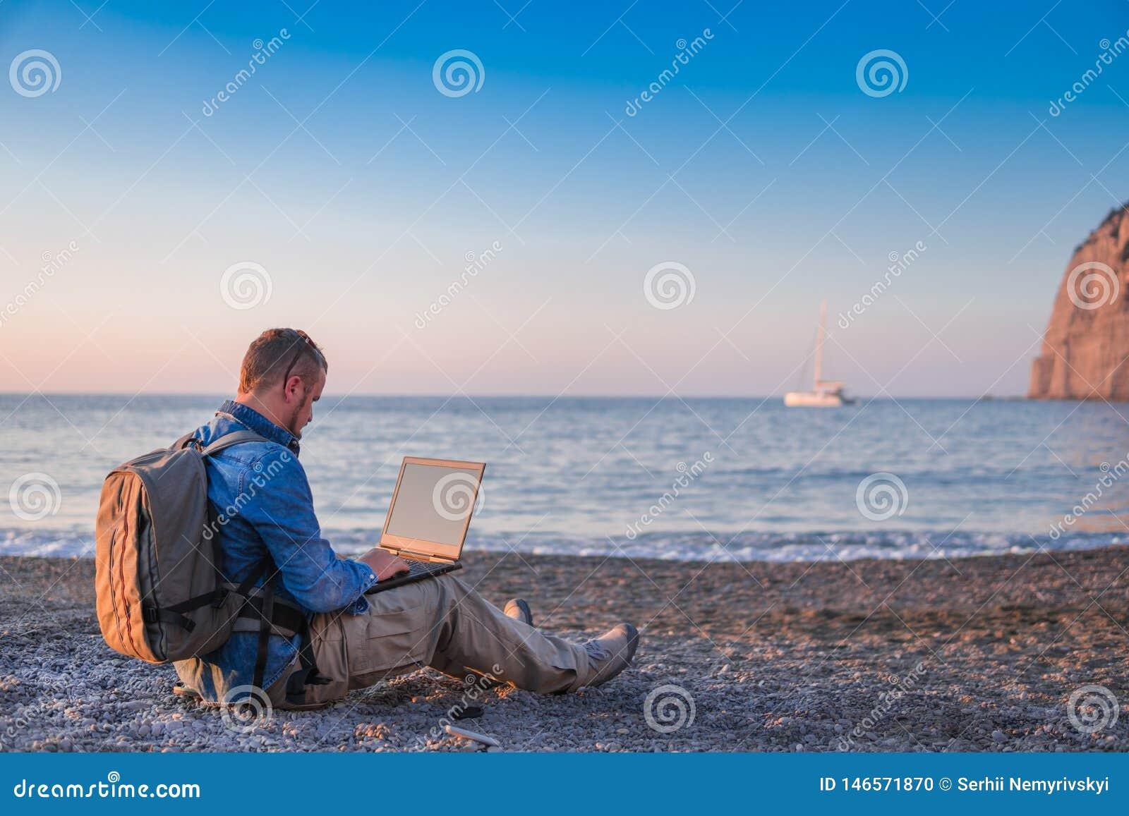 Junger Mann mit Laptopfunktion auf dem Strand Freiheit, Fernarbeits-, Freiberufler-, Technologie-, Internet-, Reise- und Ferienko