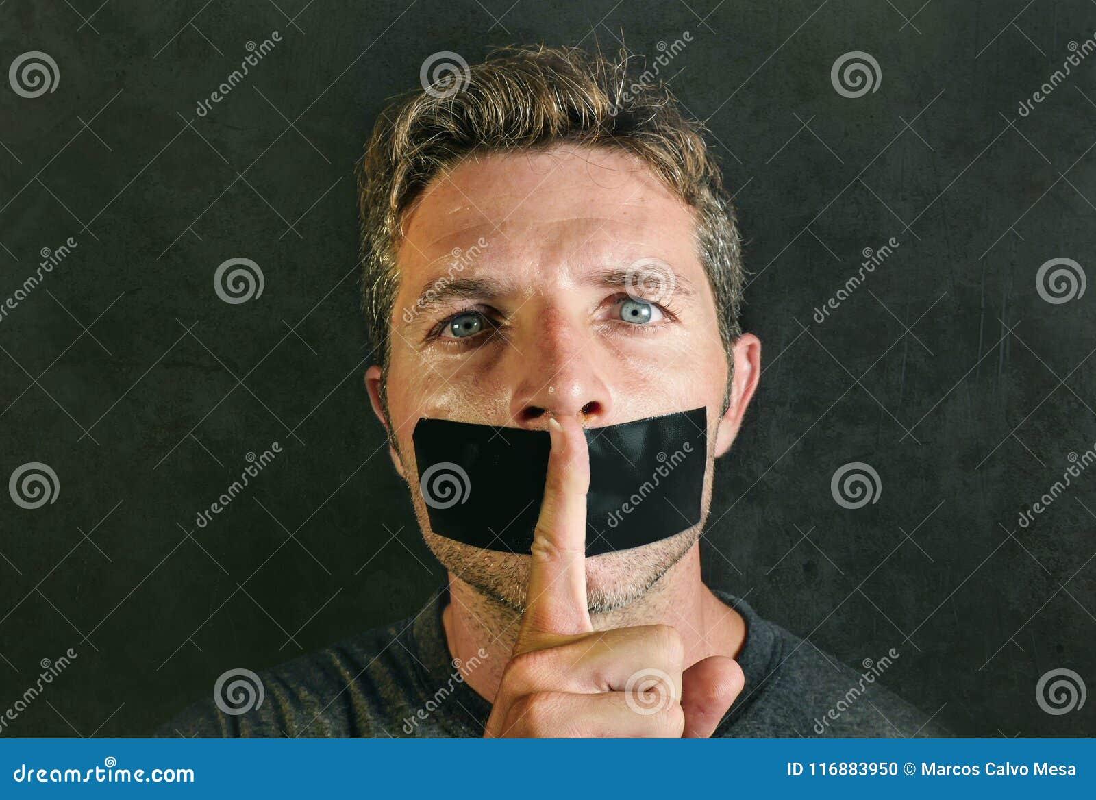 Junger Mann mit Mund und Lippen versiegelten bedeckt mit Klebstreifen in Zensur gezwungener Redefreiheit und gezwungene Ruhe und