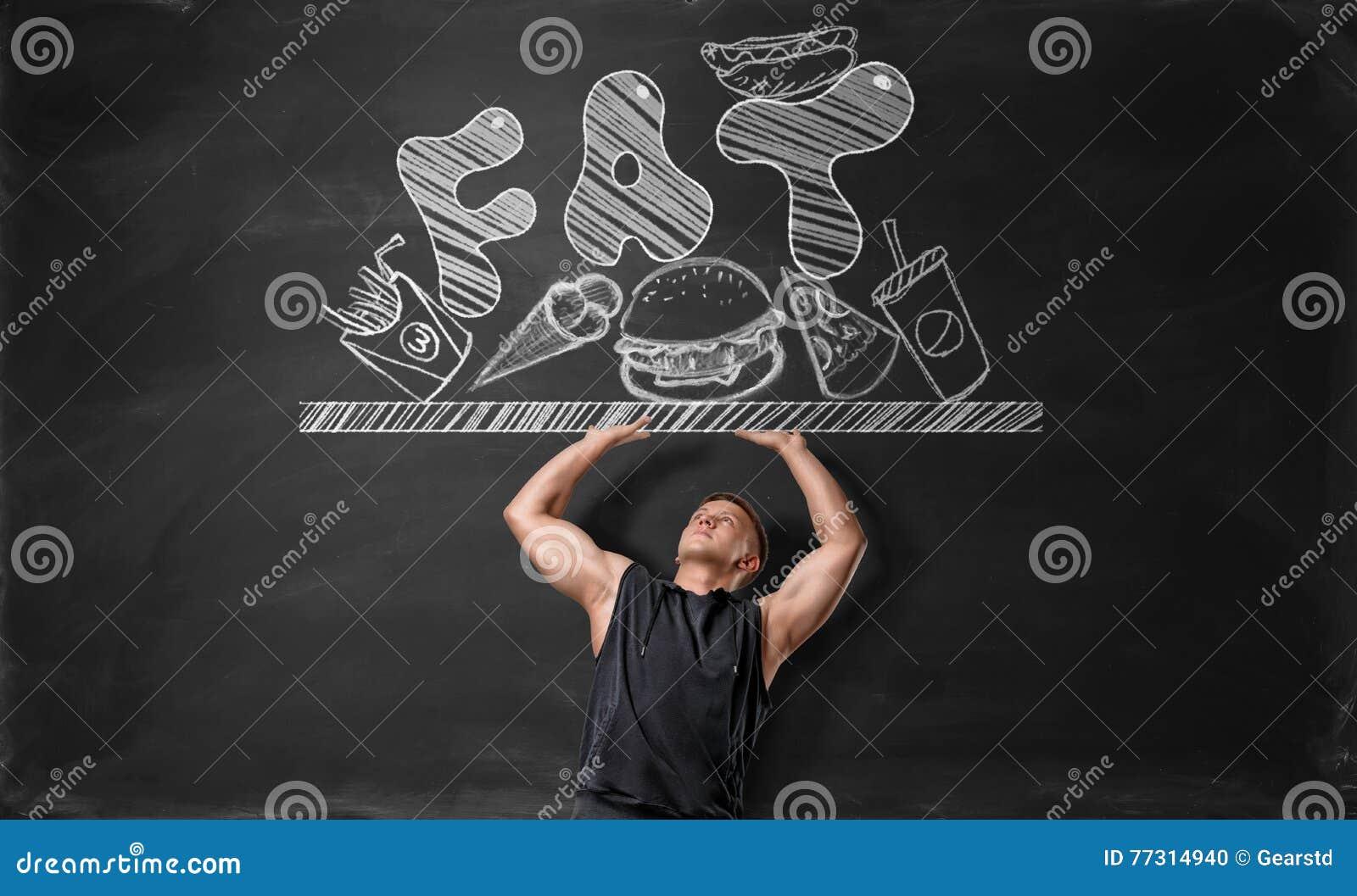 Junger Mann mit Muskeln, der weg von der Oberfläche mit ungesunder Fertigkost und Fett drückt