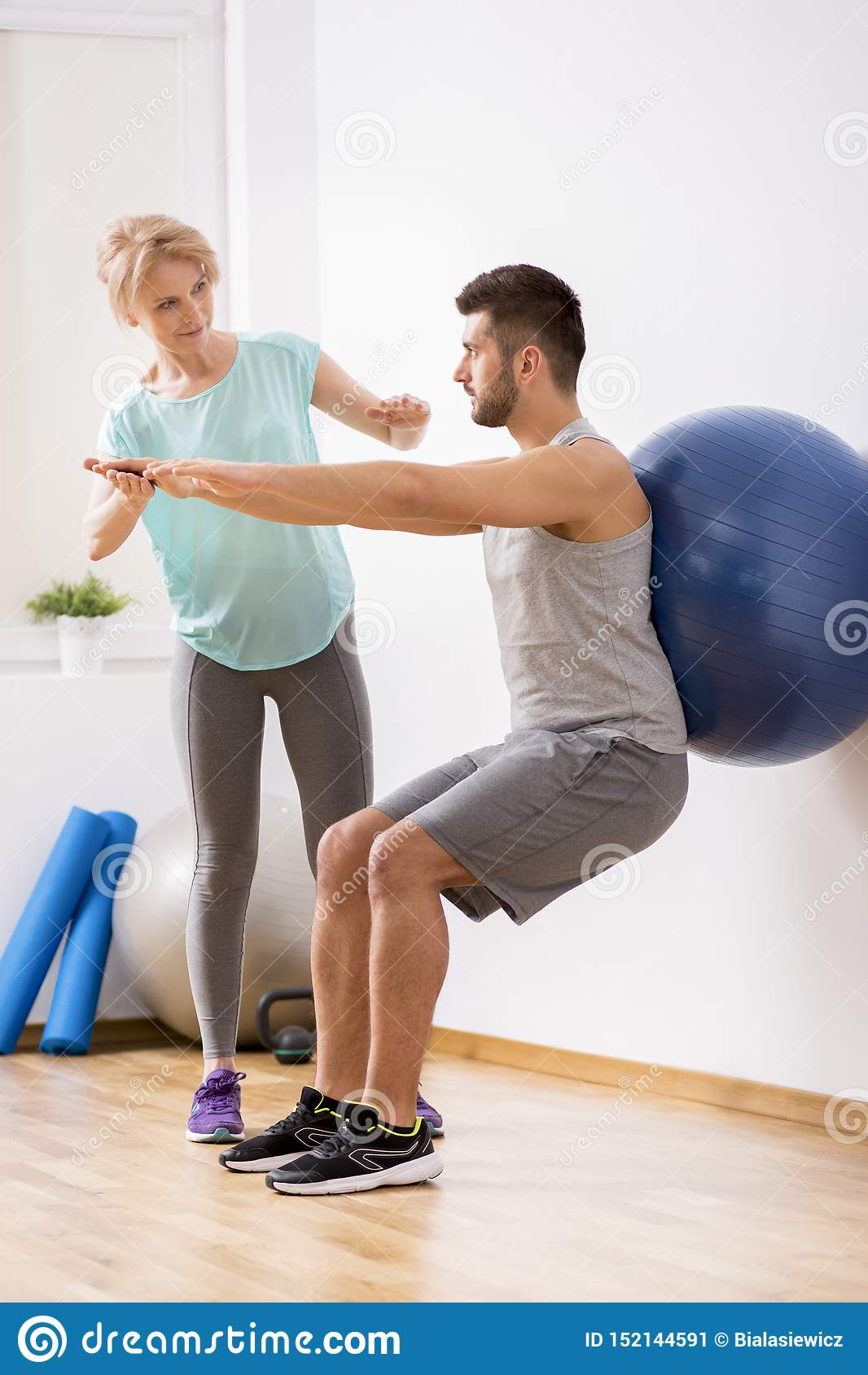 Junger Mann mit Rückenverletzung trainierend mit blauem gymnastischem Ball während der Verabredung mit weiblichem Physiotherapeut