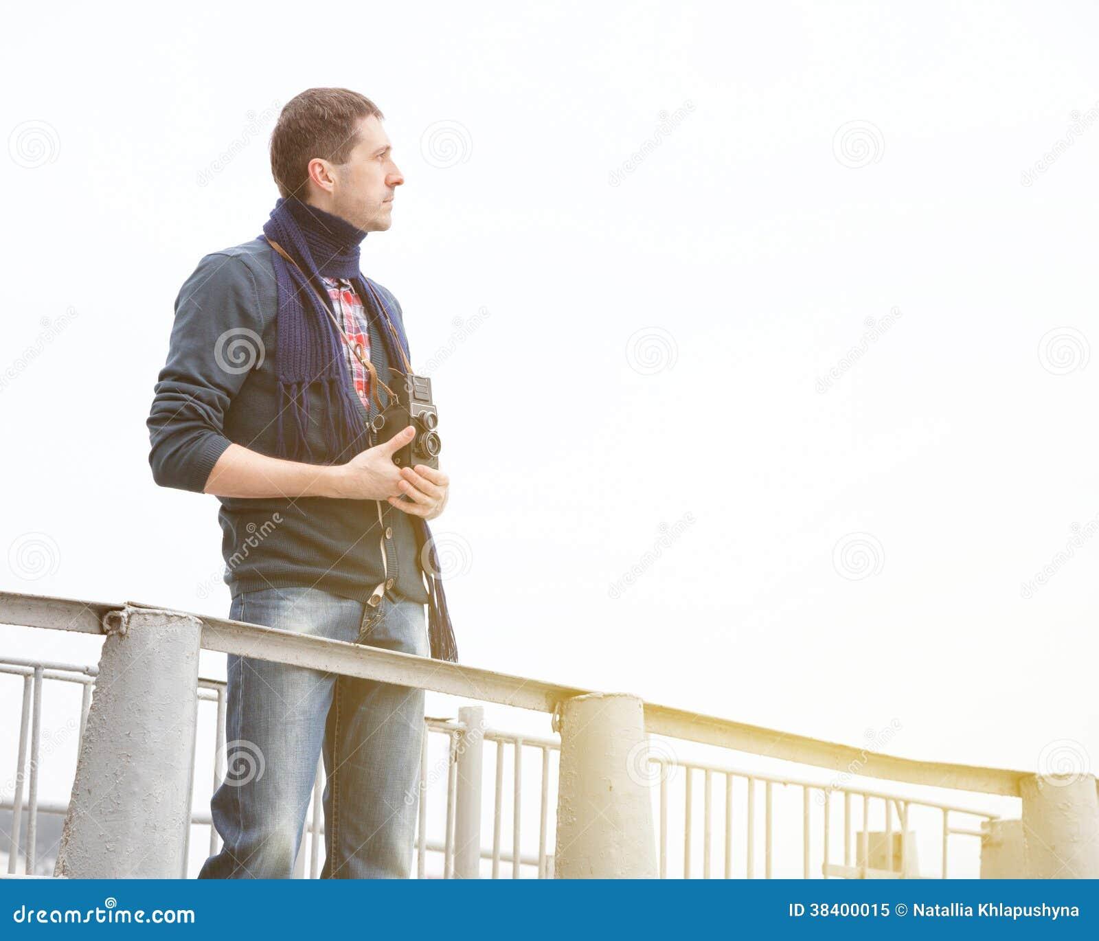 Junger Mann mit Retro- Kamera auf einer Anlegestelle