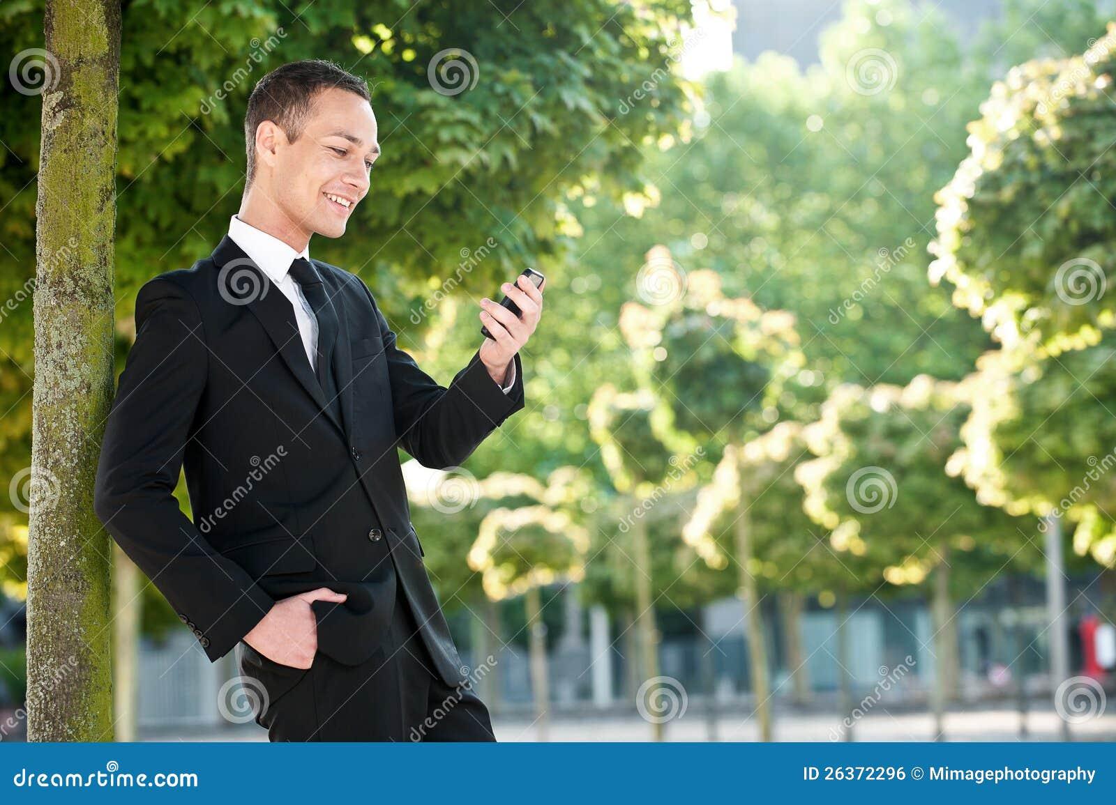 Junger Mann mit Telefon im Park