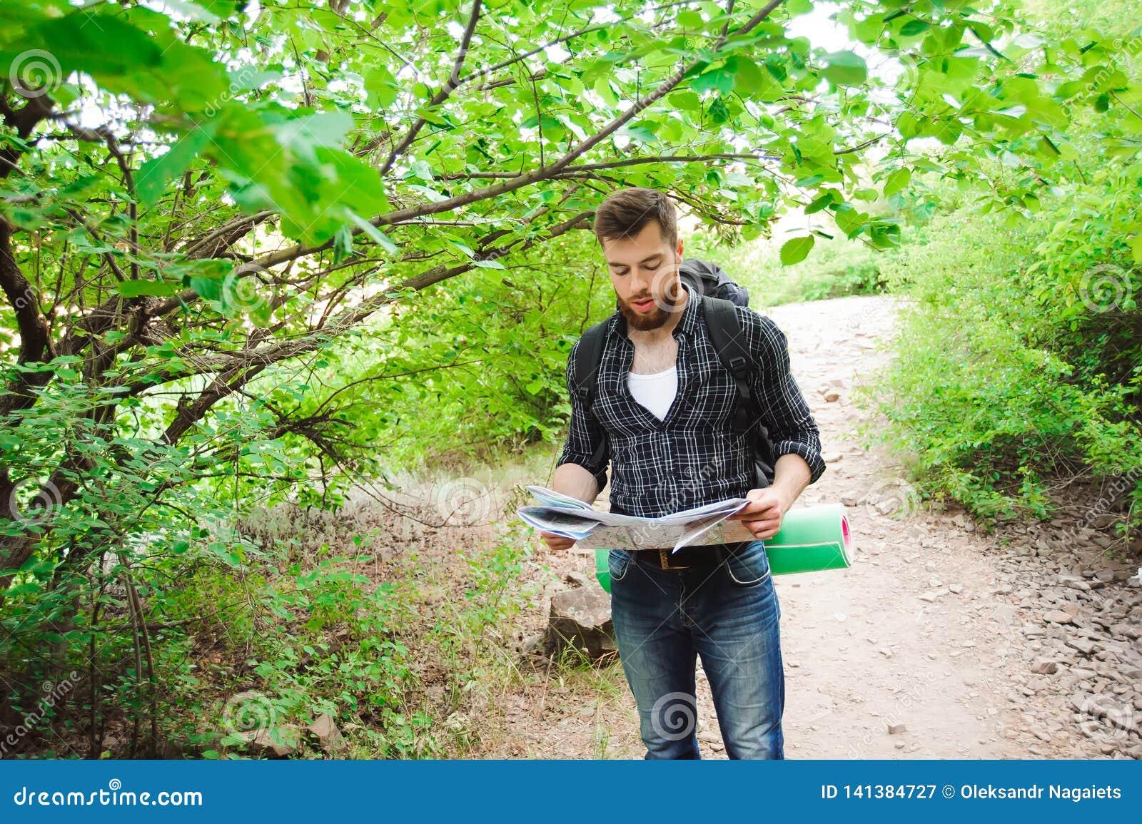 Junger Mann-Reisender mit der Kartenrucksackentspannung im Freien auf den Hintergrundsommerferien und Lebensstil Konzept wandernd