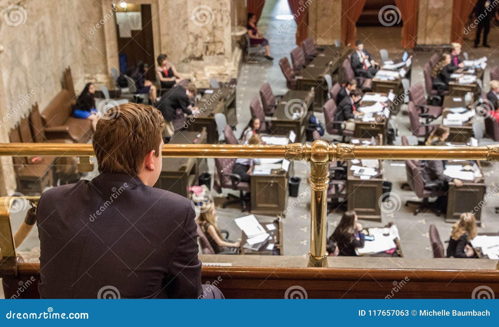 Junger Mann sitzt in der Galerie und passt Gesetzgebungsverfahren auf