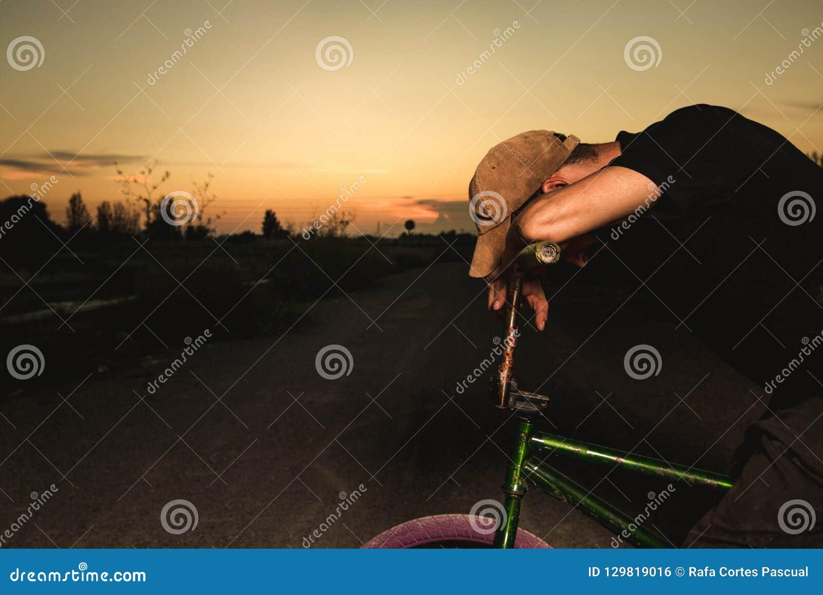 Junger Mann stehendes bmx Fahrrad BMX-Reiter mit und ein Sonnenuntergang