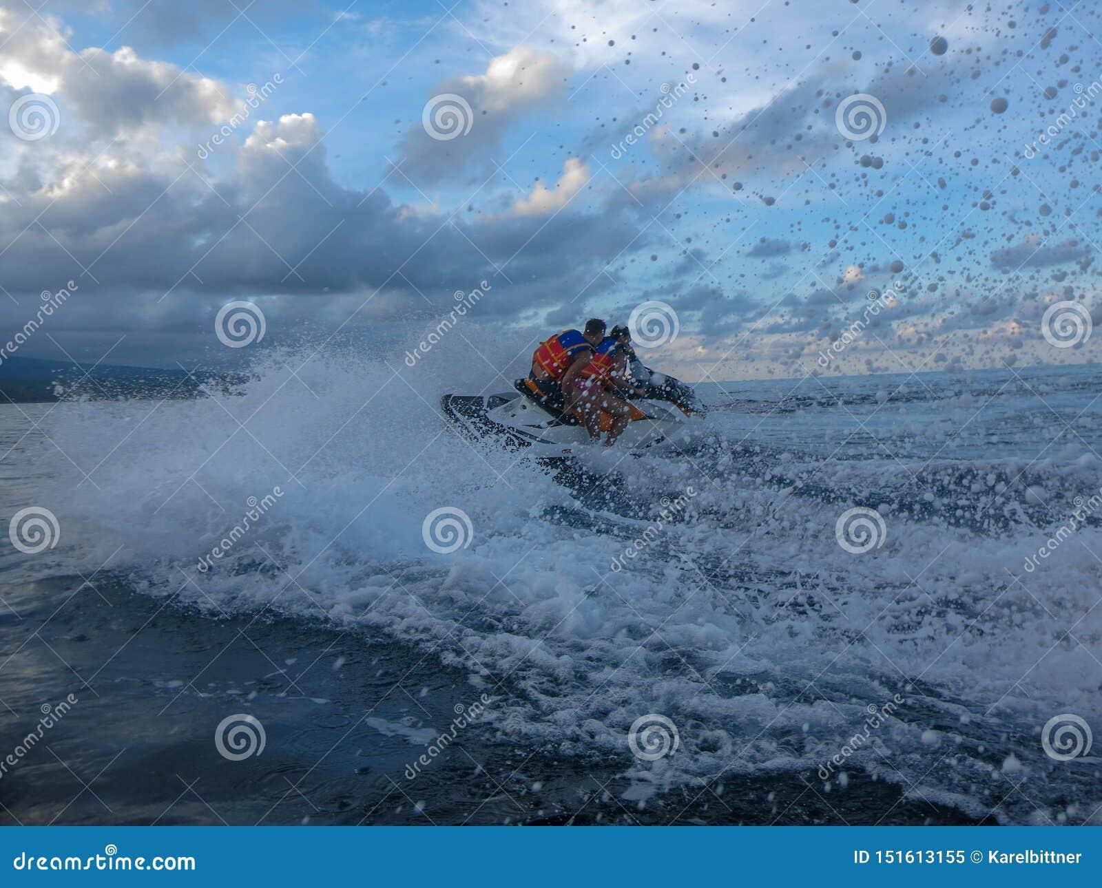 Junger Mann und Frau, die über der Oberfläche treibt Leute auf Jet Ski haben Spaß im Ozean Fahrer in der Aktion während des Sprit