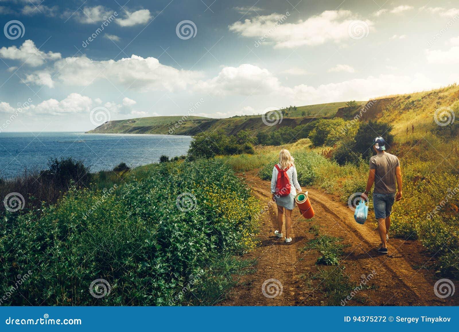 Junger Mann und Frau mit dem Rucksack, Ansicht von hinten, gehend entlang die Straße in Richtung zu den Seeabenteuerreisen entspa