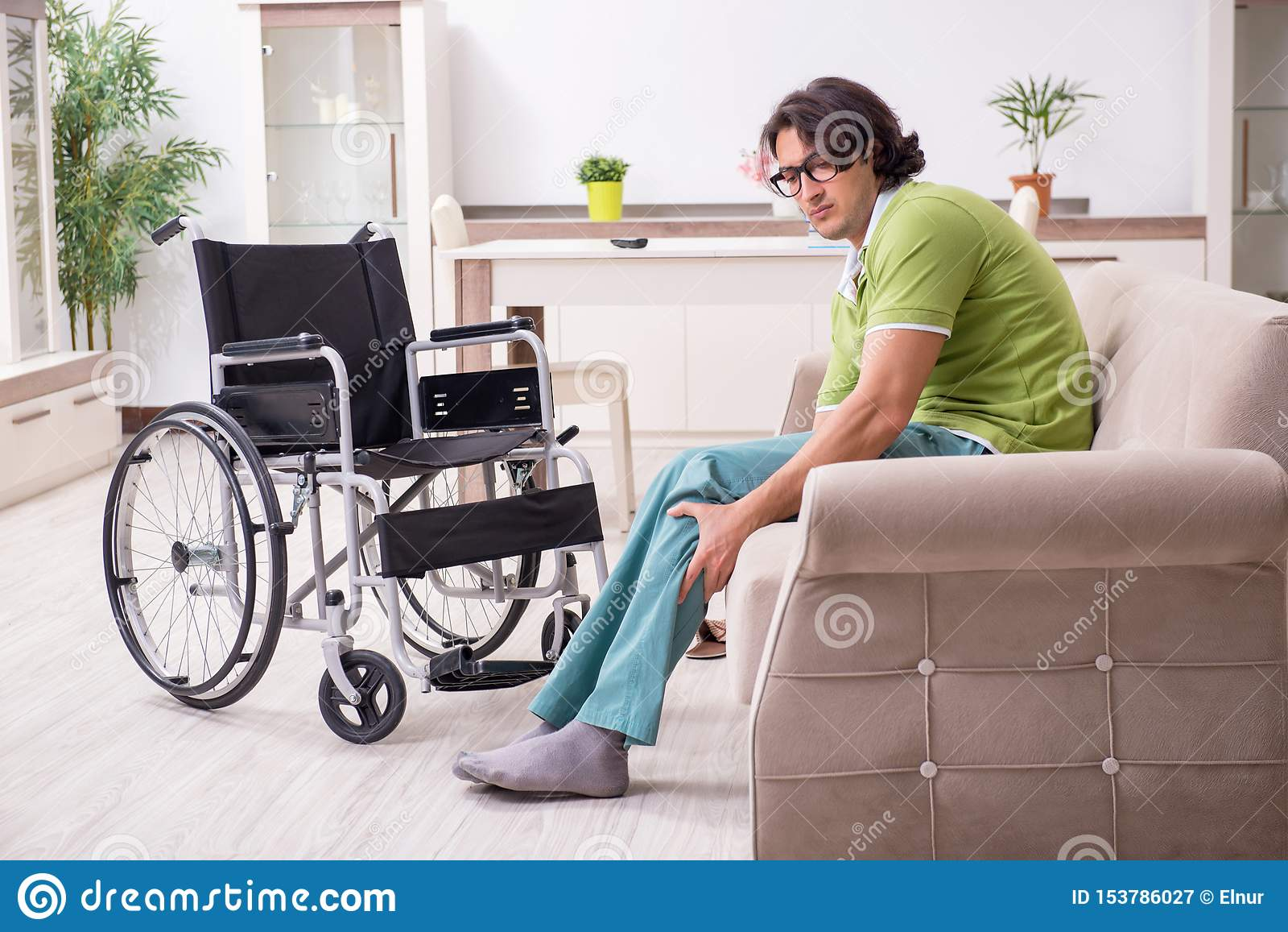 Junger Mann ungültig im Rollstuhl, der zu Hause leidet