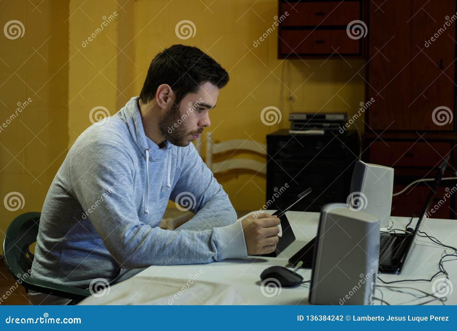 Junger Mann unter Verwendung seines Mobiles, Tablette, Laptops und Kopfhörer