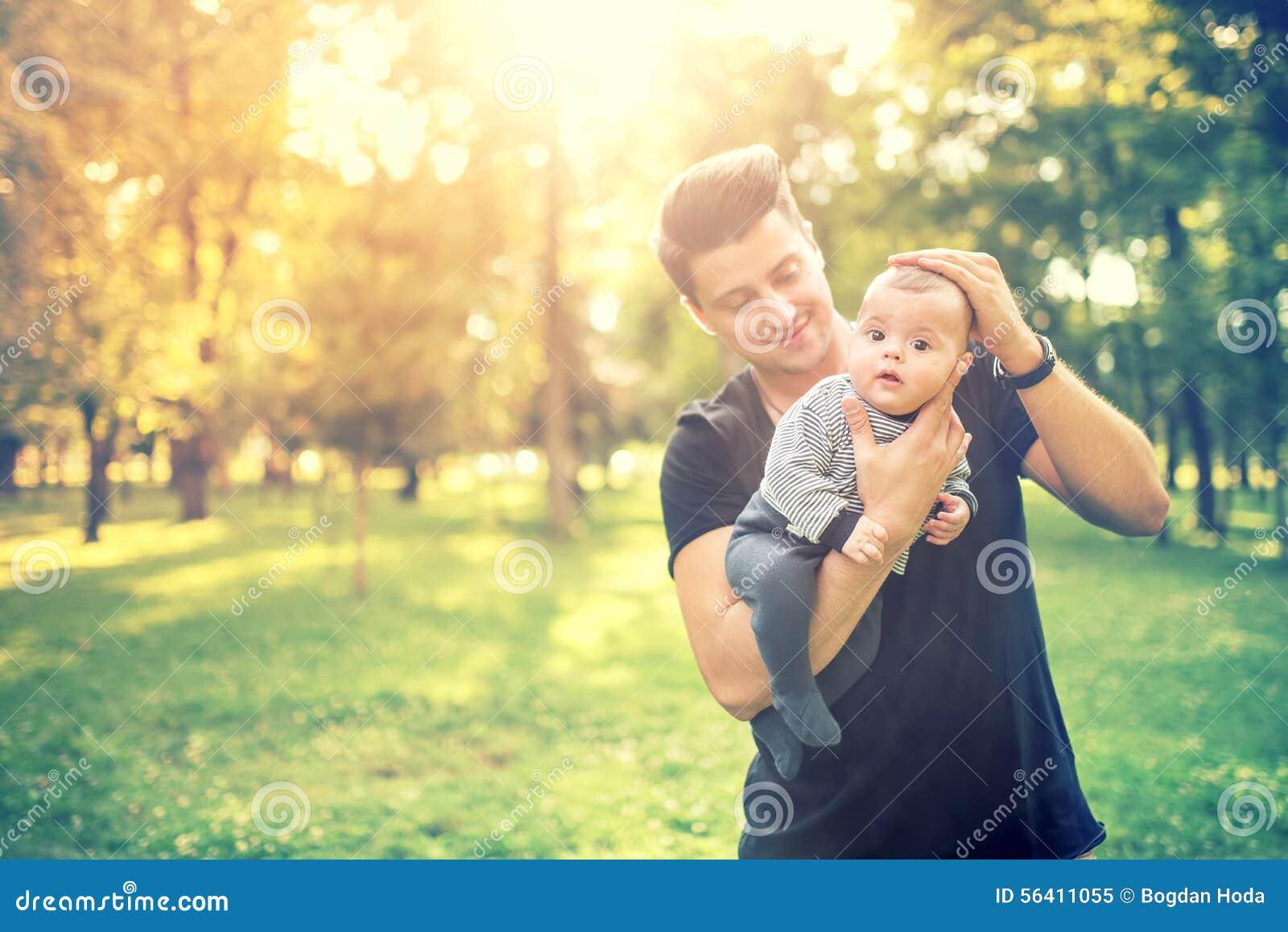 Junger Mann, Vater, der 3 Monate alte Kind hält und eine gute Zeit im Park hat Vater- und Sohnkonzept in der Natur