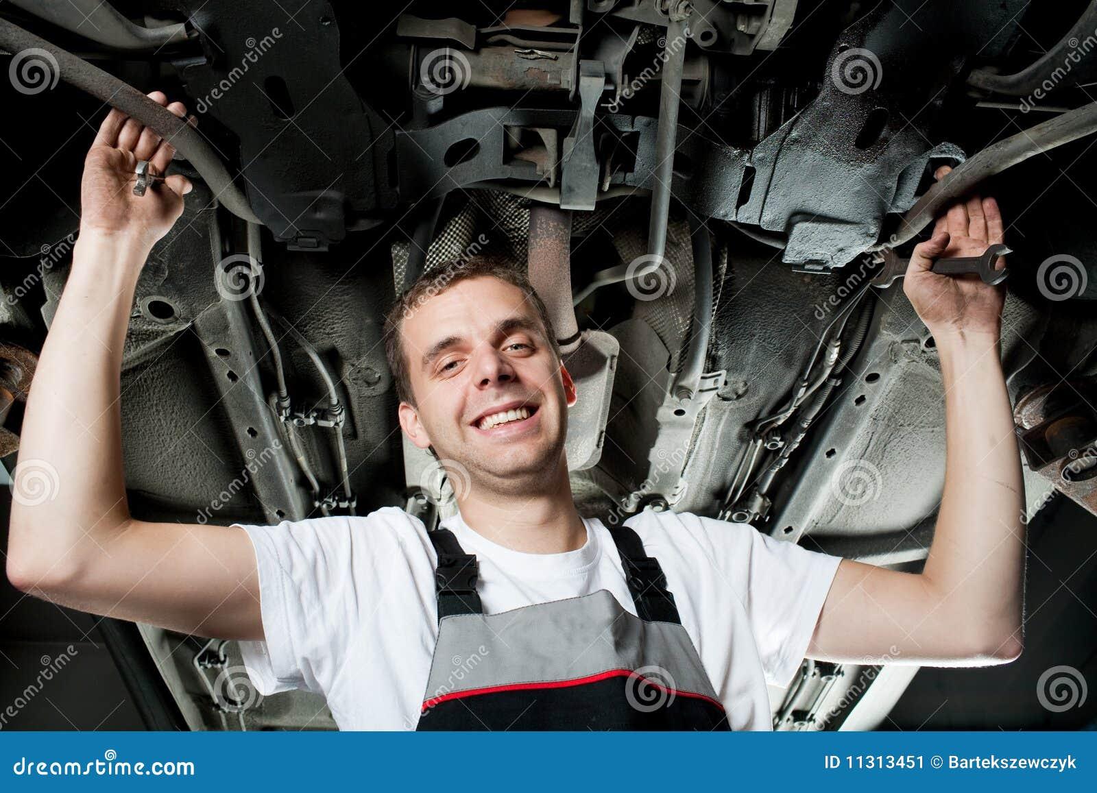 Junger Mechaniker, der unter dem Auto in der Garage arbeitet