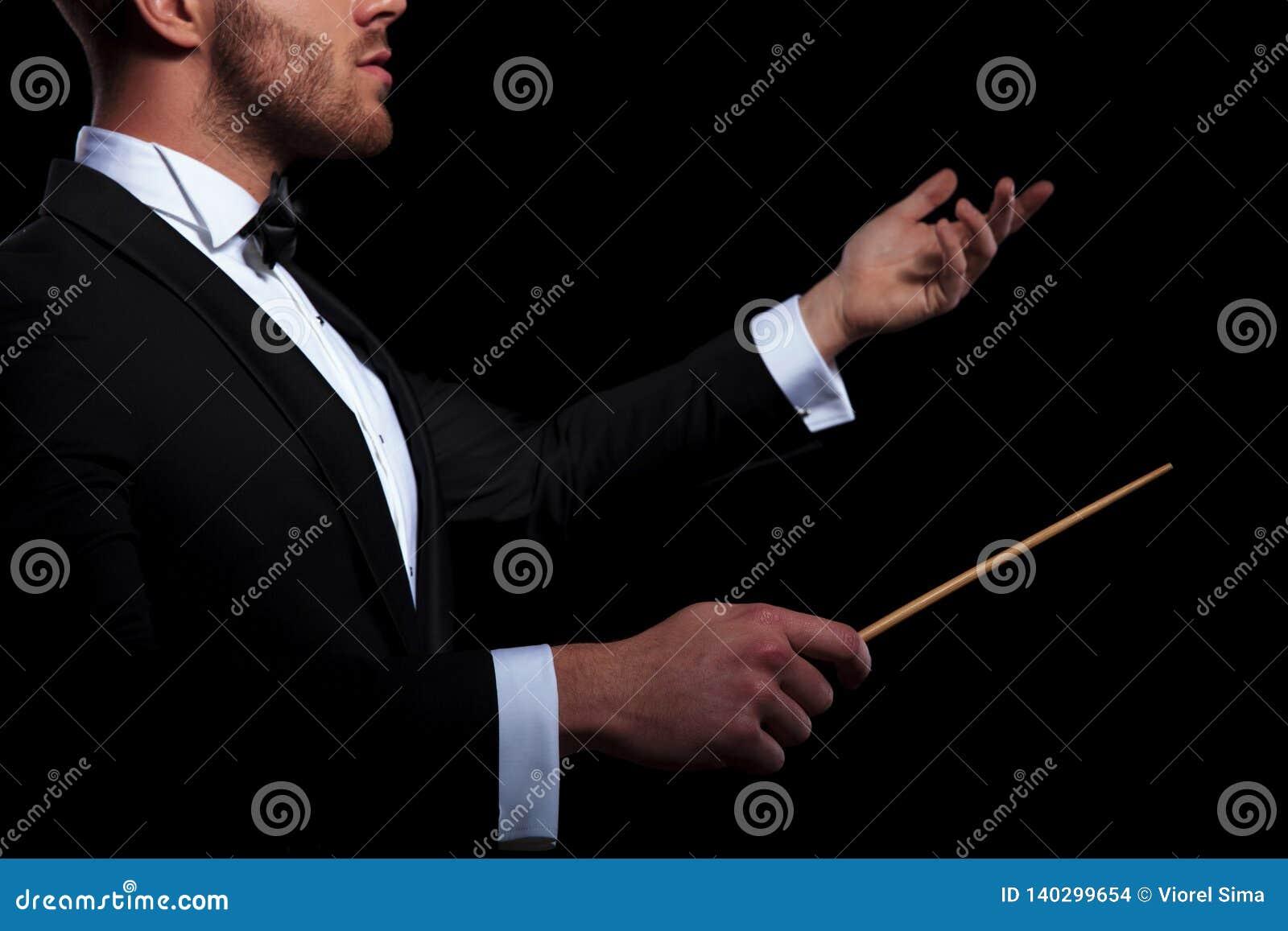 Junger Musiker, der unter Verwendung eines Stockes und eines Gestikulierens leitet