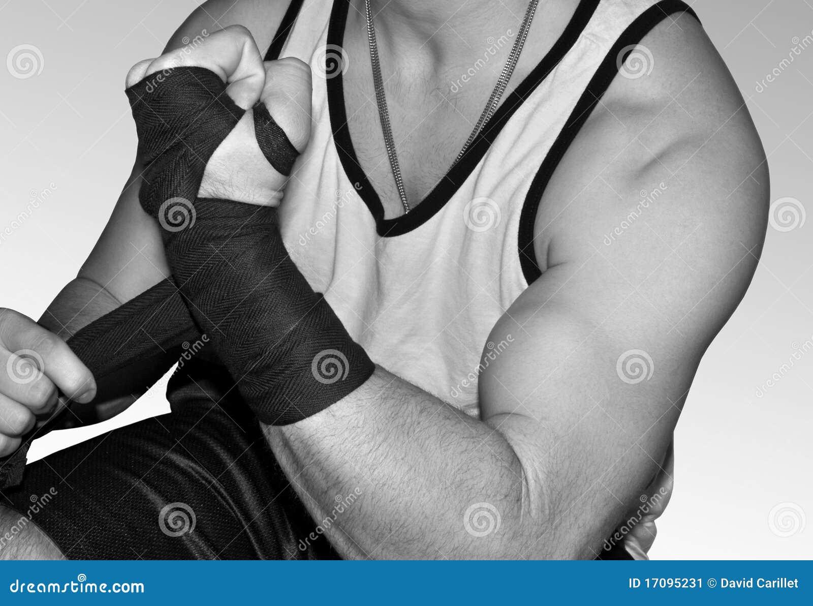 Junger muskulöser Kämpfer, der Handgelenke für MMA einwickelt