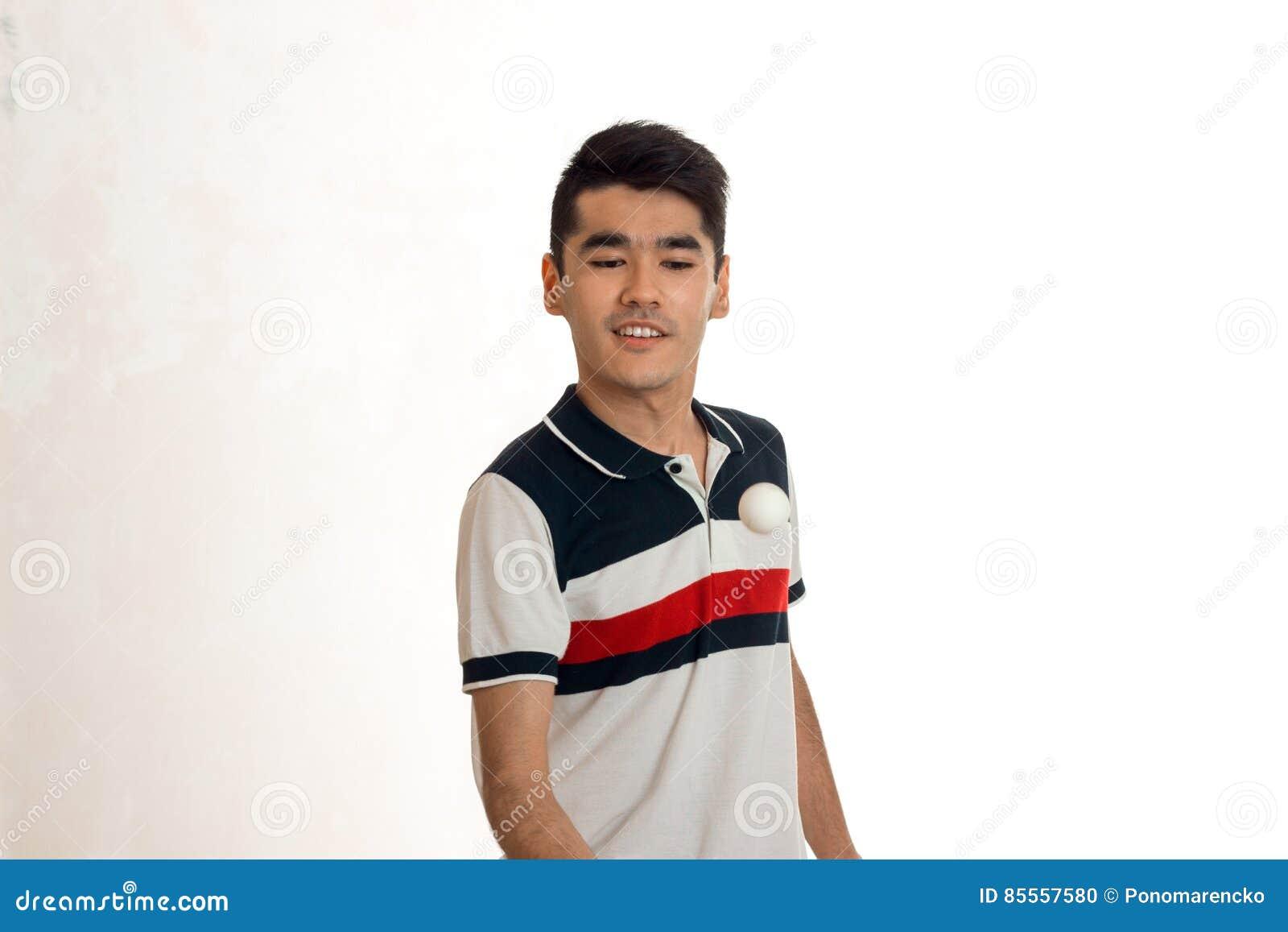 Junger netter Mann, der das Tischtennis lokalisiert auf weißem Hintergrund im Studio spielt