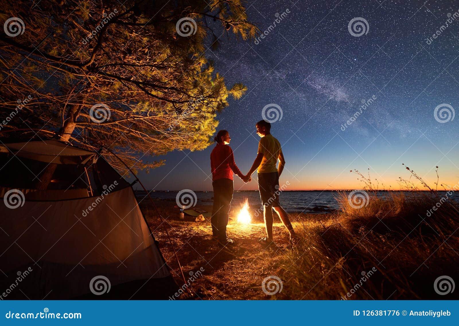 Junger Paarmann und -frau, die Rest am touristischen Zelt und an brennendem Lagerfeuer auf Seeufer nahe Wald hat