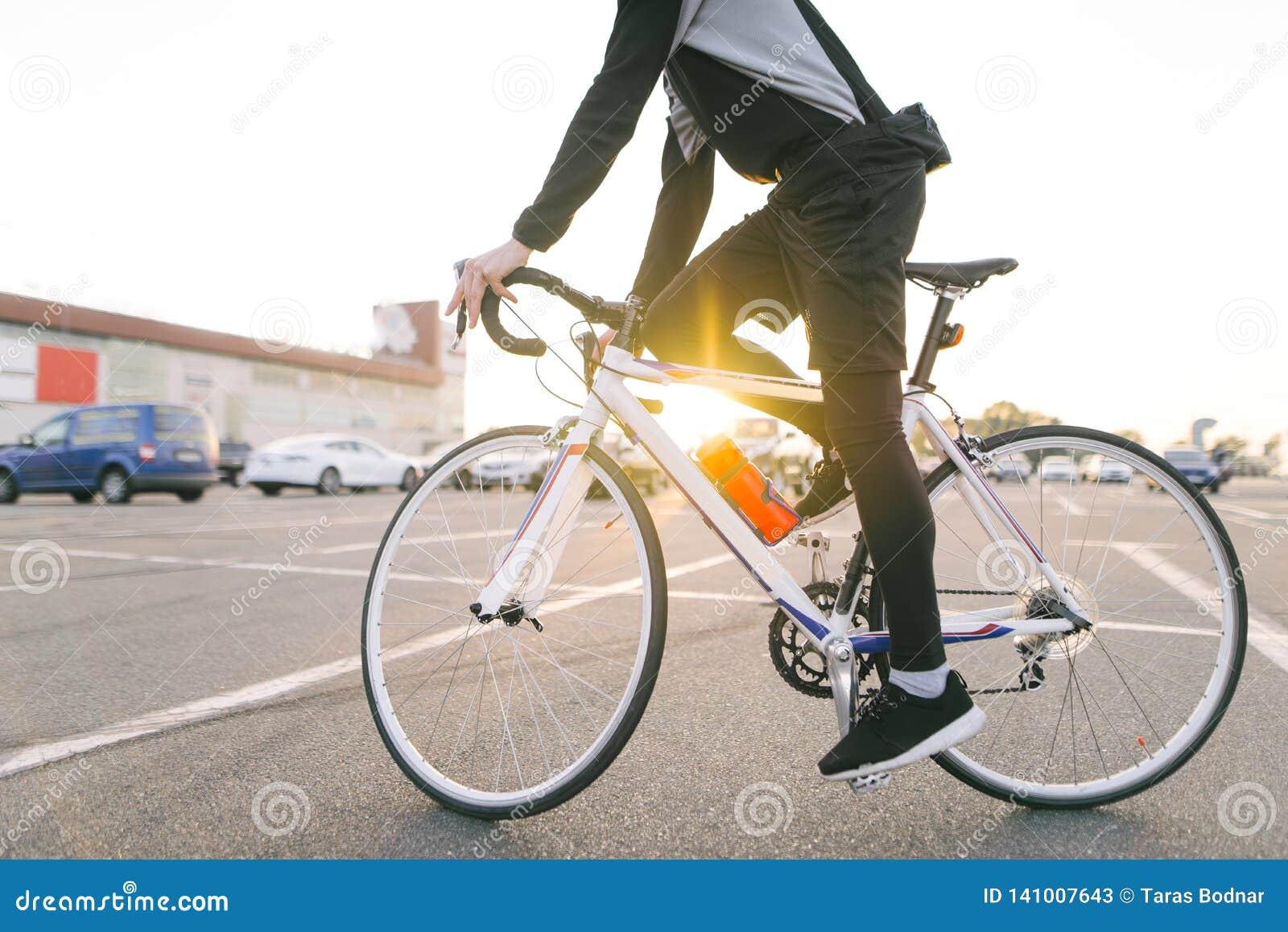 Junger Reiter im dunklen Fahrrad trägt ein Fahrrad auf einem Straßenhintergrund und -sonnenschein im Sonnenuntergang