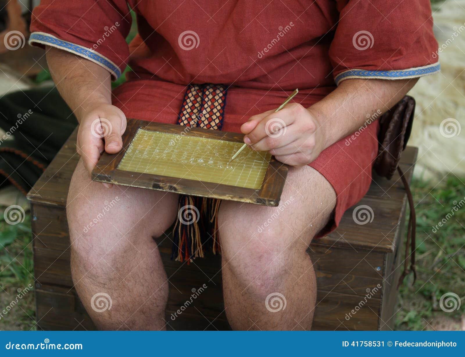 Junger SCHREIBER schreibt auf ein Wachs Tablet