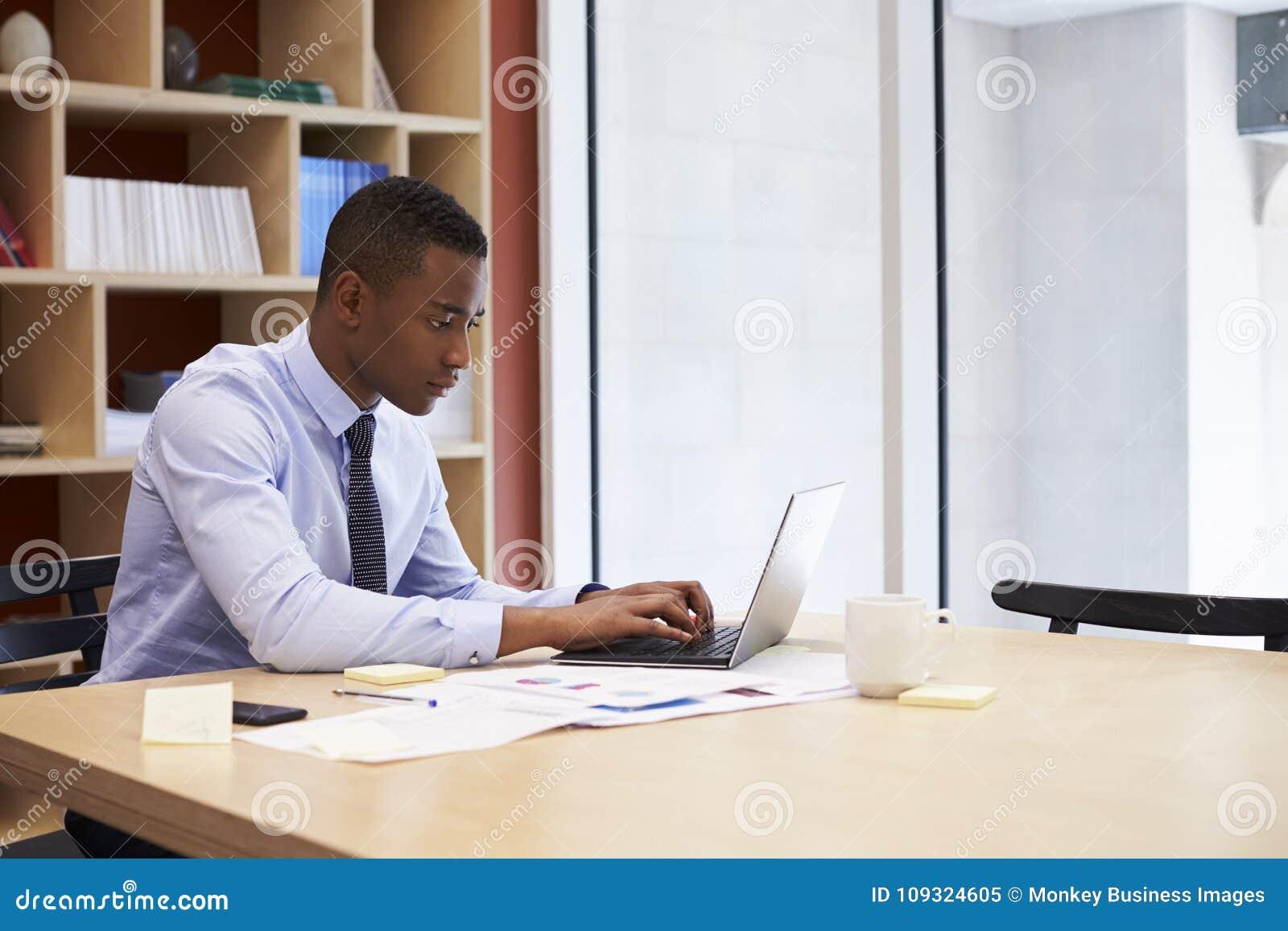 Junger schwarzer Geschäftsmann, der allein oben in einem Büro, Abschluss arbeitet