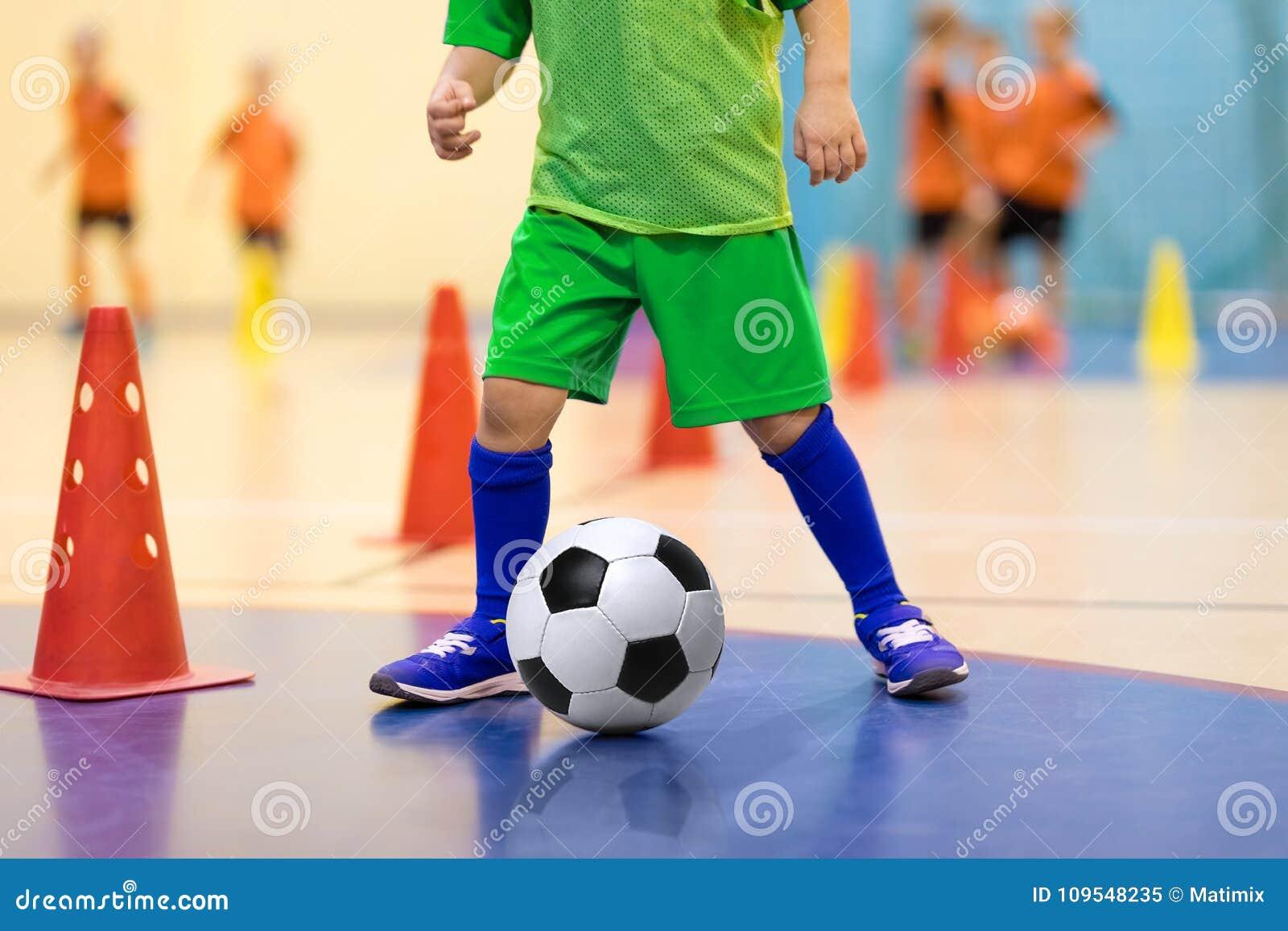 Junger Spieler des Hallenfußballs mit einem Fußball in einer Sporthalle Spieler in der grünen Uniform Basketball mit Metallflügel