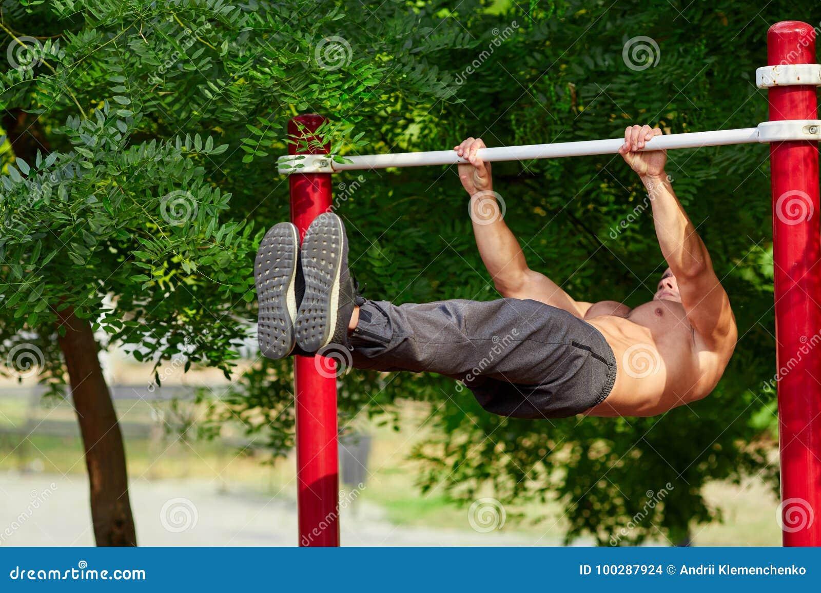Junger starker Mann tut ZugUPS auf einer horizontalen Stange auf einem Sportplatz im Sommer in der Stadt