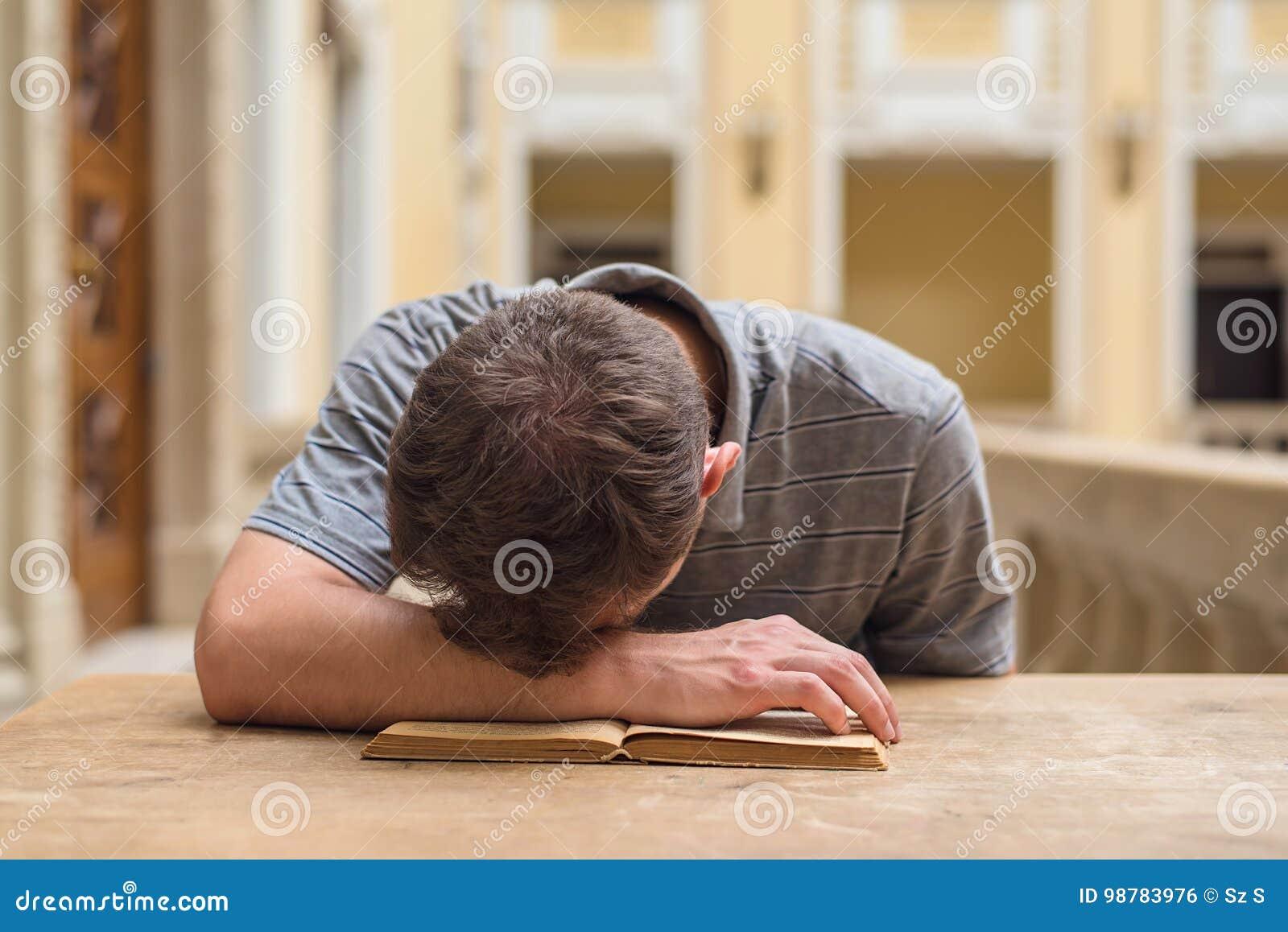 Junger Studentenkerl, der ein langweiliges Thema studiert