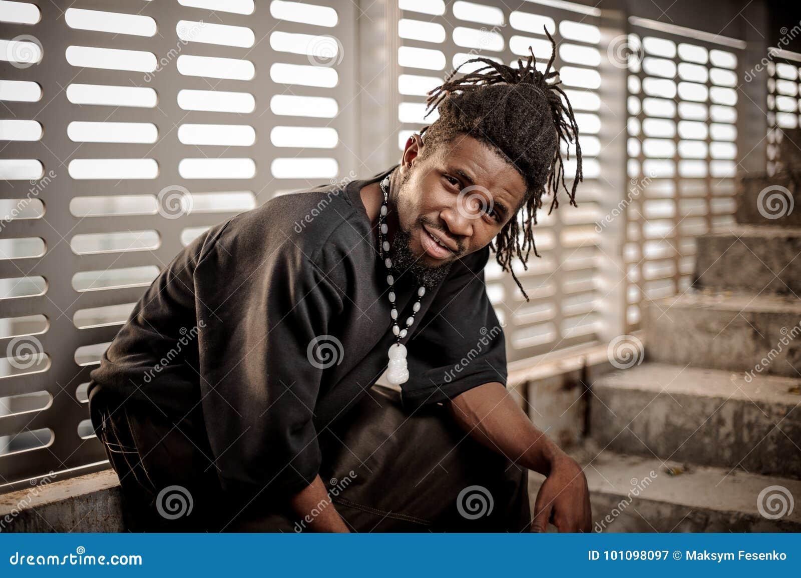 Junger und attraktiver Afroamerikanermann, der nahe dem Fenster sitzt