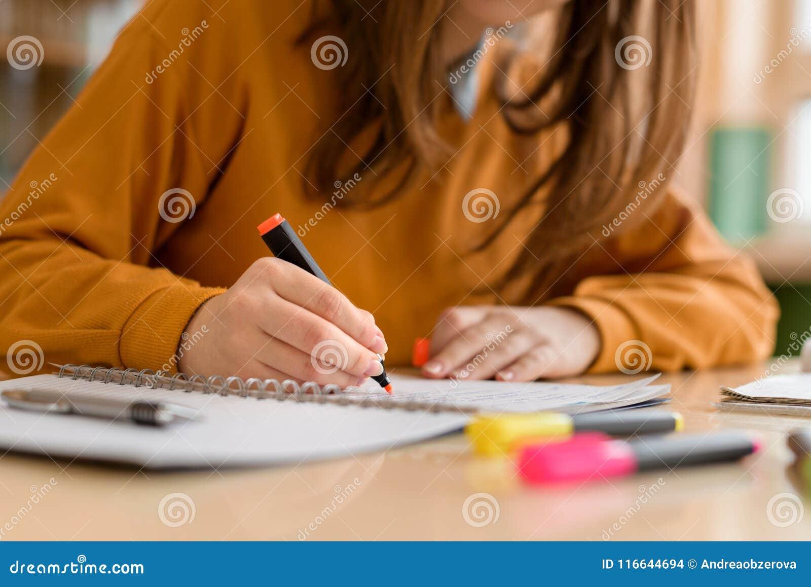 Junger unrecognisable weiblicher Student in der Klasse, Kenntnisse nehmend und verwenden Leuchtmarker Fokussierter Student im Kla