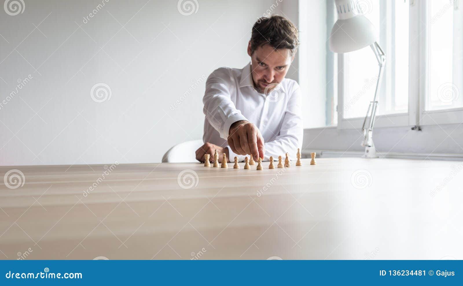 Junger Unternehmensleiter, der weiße Schachfiguren in einer vernünftigen Struktur in Position bringt
