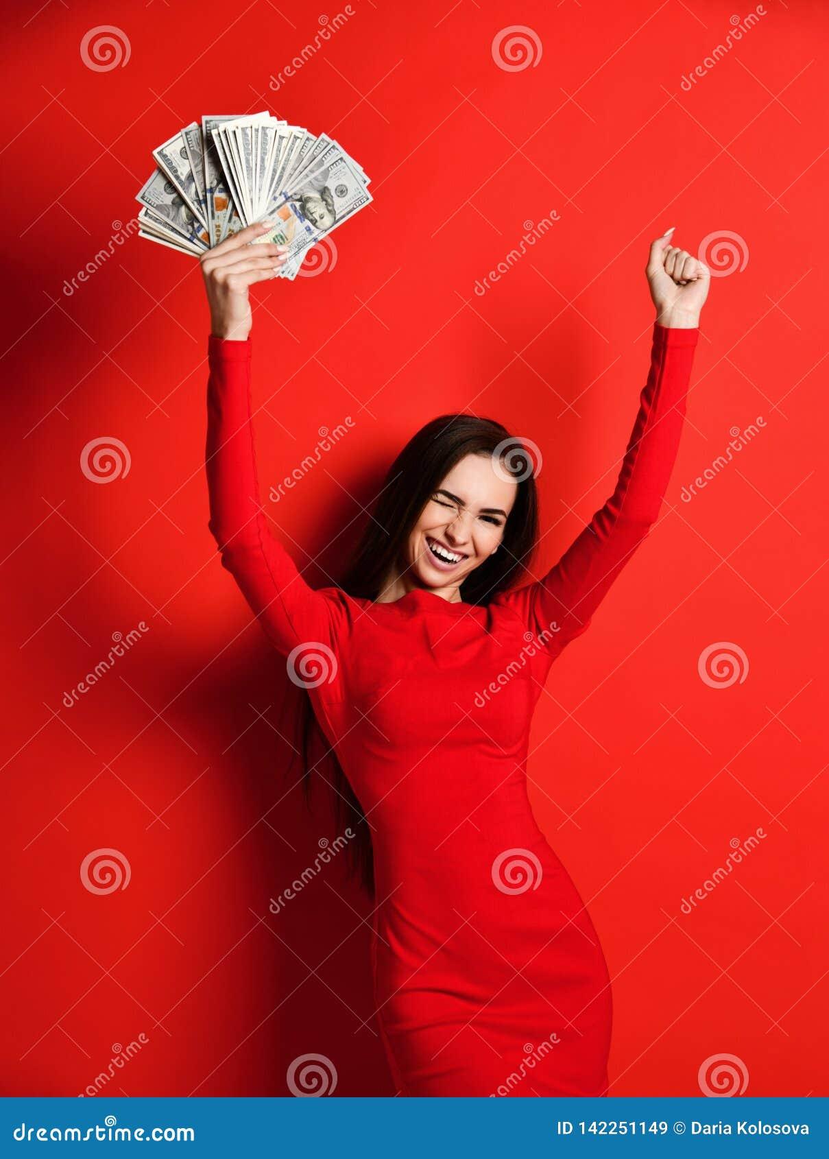 Junger unverschämter Brunette in einem roten Kleid freut sich in einem großen Geldbetrag in ihren Händen, die sie gewinnt