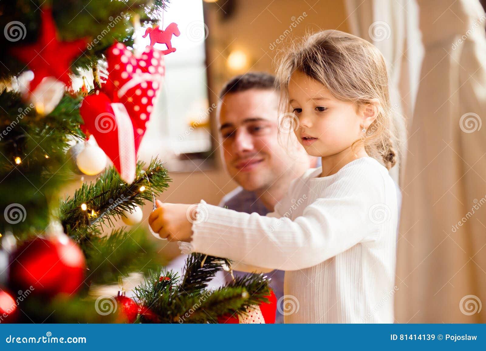 Junger Vater mit daugter Weihnachtsbaum zusammen verzierend
