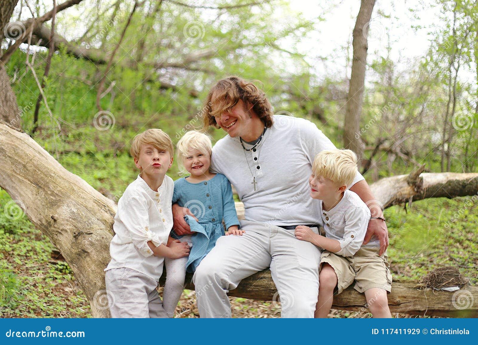 Junger Vater und seine drei glückliche Kinder, die O spielen und lachen