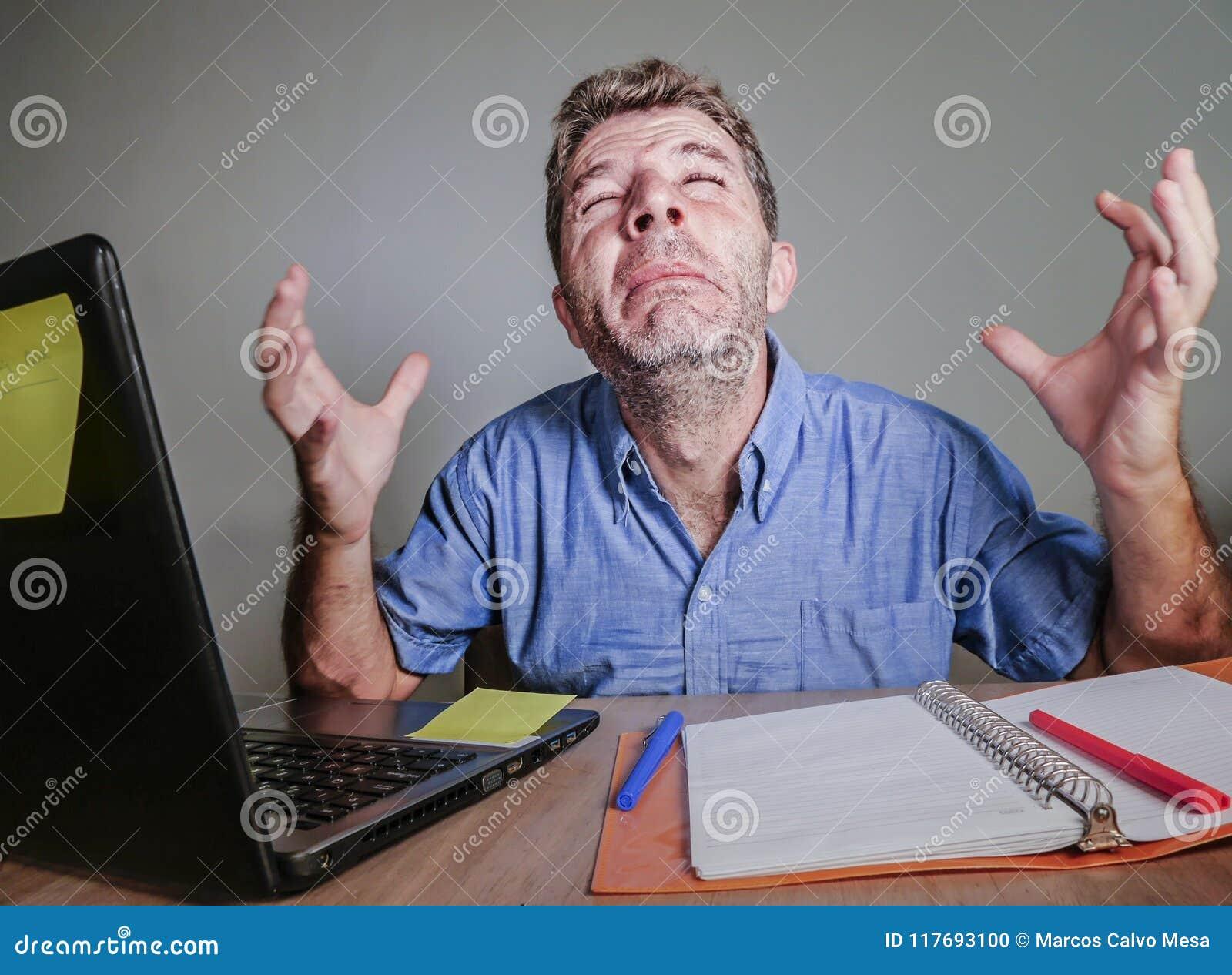 Junger verrückter betonter und überwältigter Mann, der das unordentliche Schreien hoffnungslos mit Laptop-Computer Gefühl erschöp