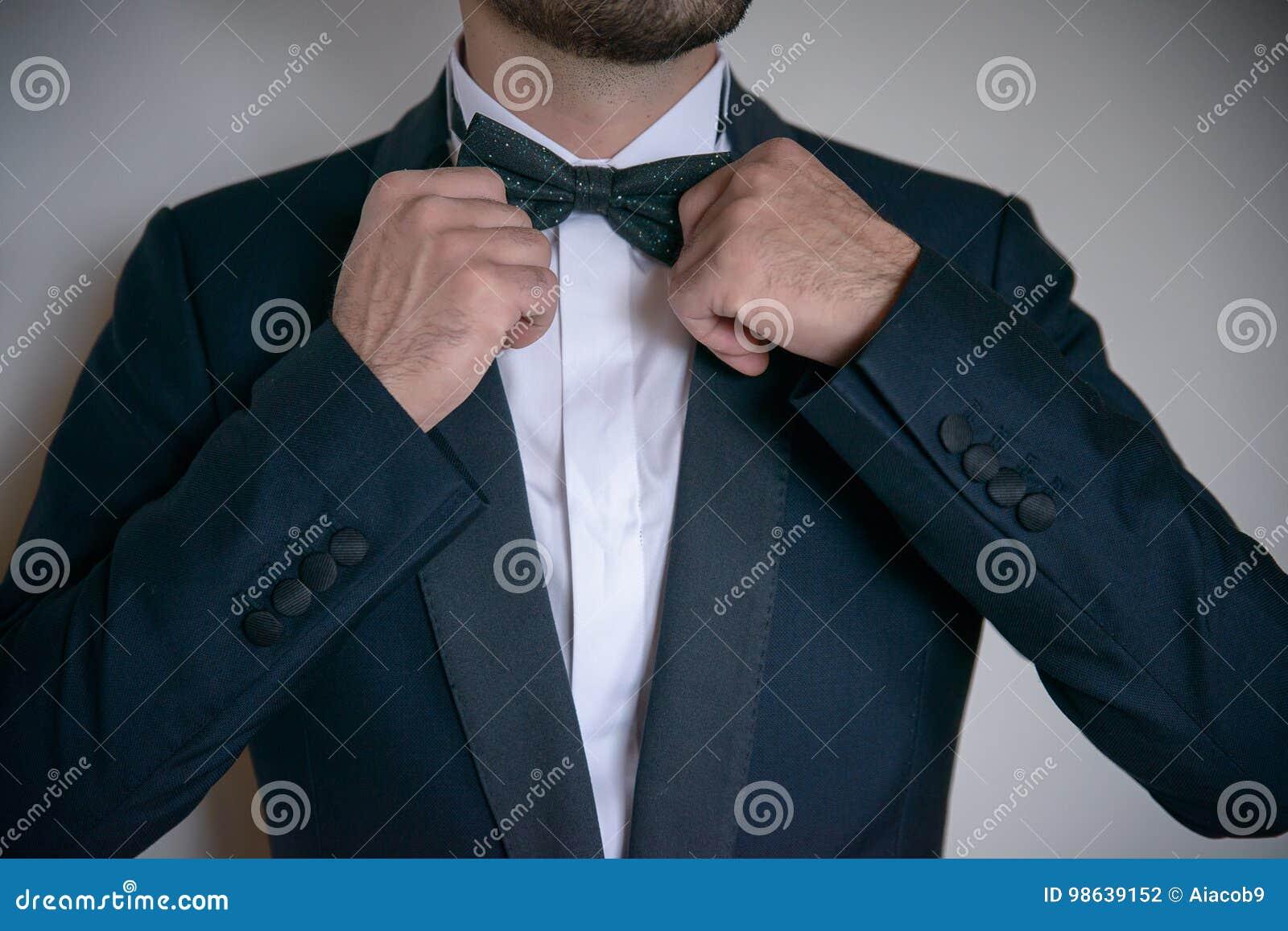 Junger weißer kaukasischer Mann, der seine Fliege in Bestellung einsetzt und formale, elegante Kleidung trägt