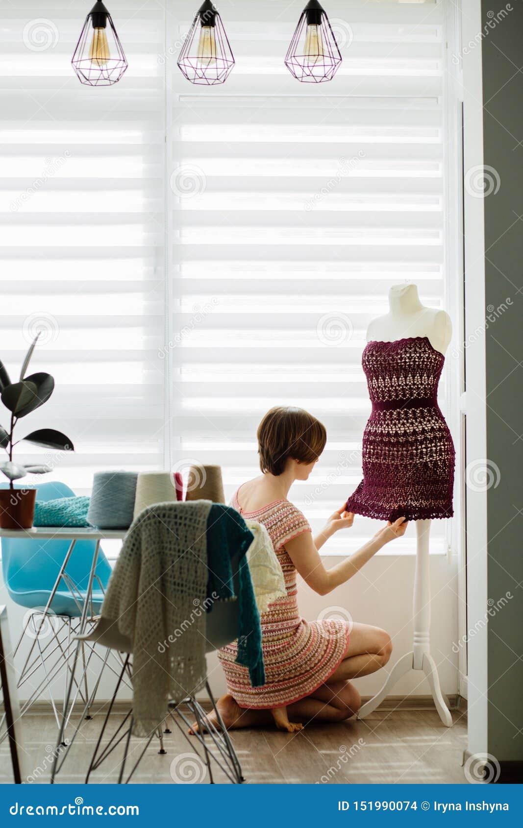 Junger weiblicher Kleidungsdesigner, der Kleiderattrappe am gemütlichen Hauptinnen-, freiberuflich tätigen Lebensstil verwendet V