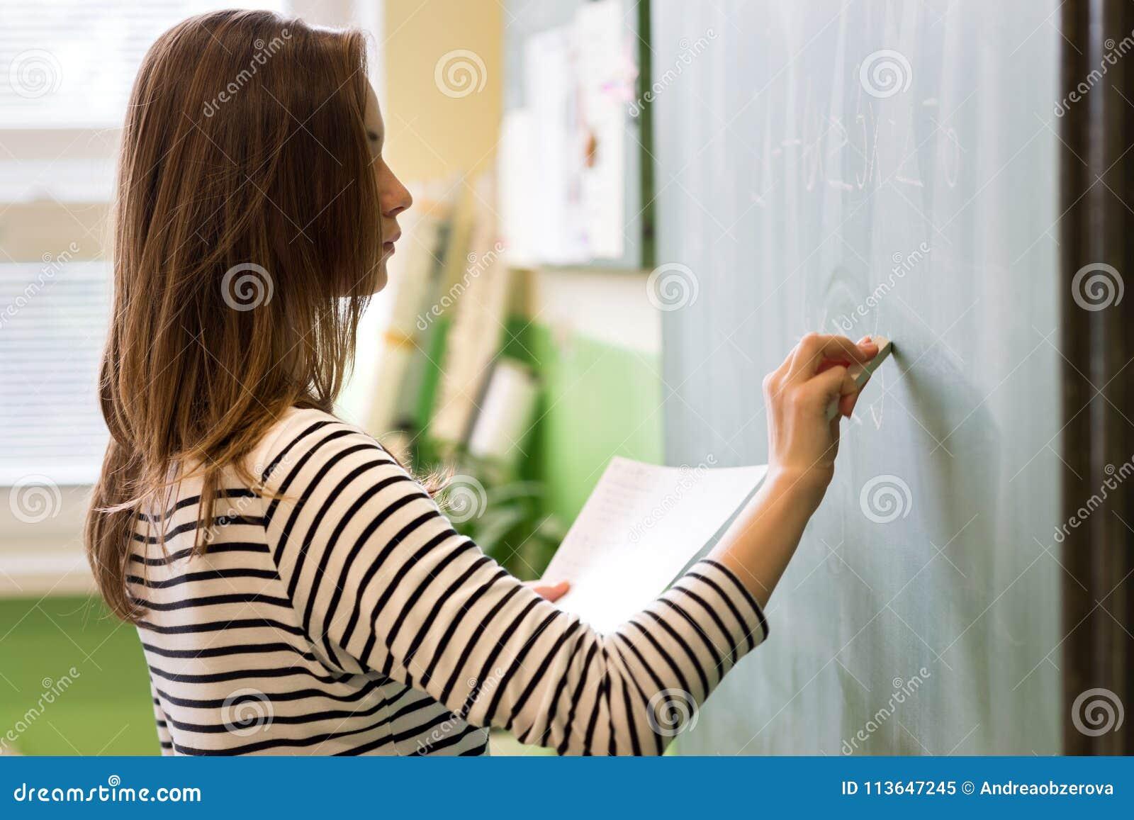 Junger weiblicher Lehrer oder eine Studentenschreibensmatheformel auf Tafel