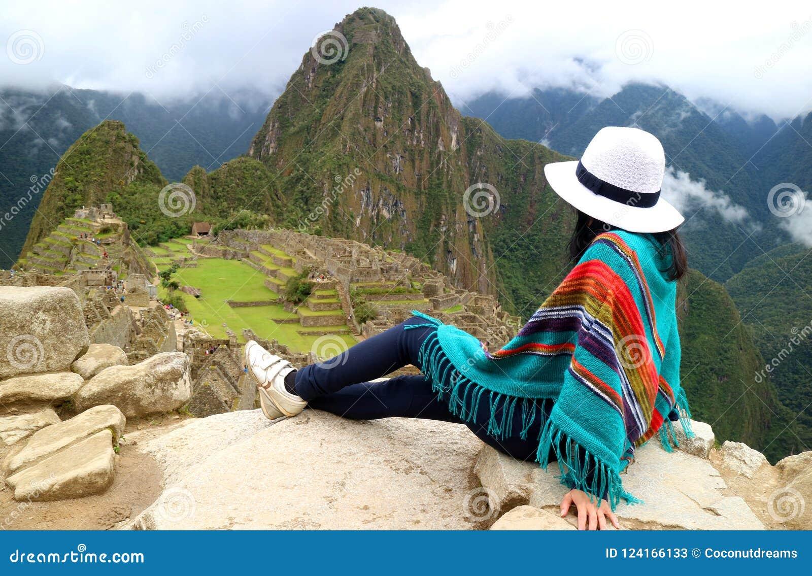 Junger weiblicher Reisender, der die Inkaruinen von Machu Picchu, einer des neuen Wunders sieben der Welt, Cusco-Region bewundert