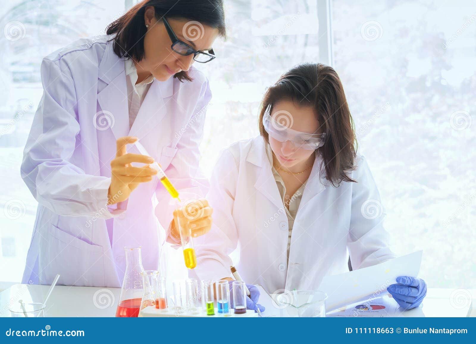 Junger weiblicher Wissenschaftler, der mit techer bei der Laborantherstellung steht